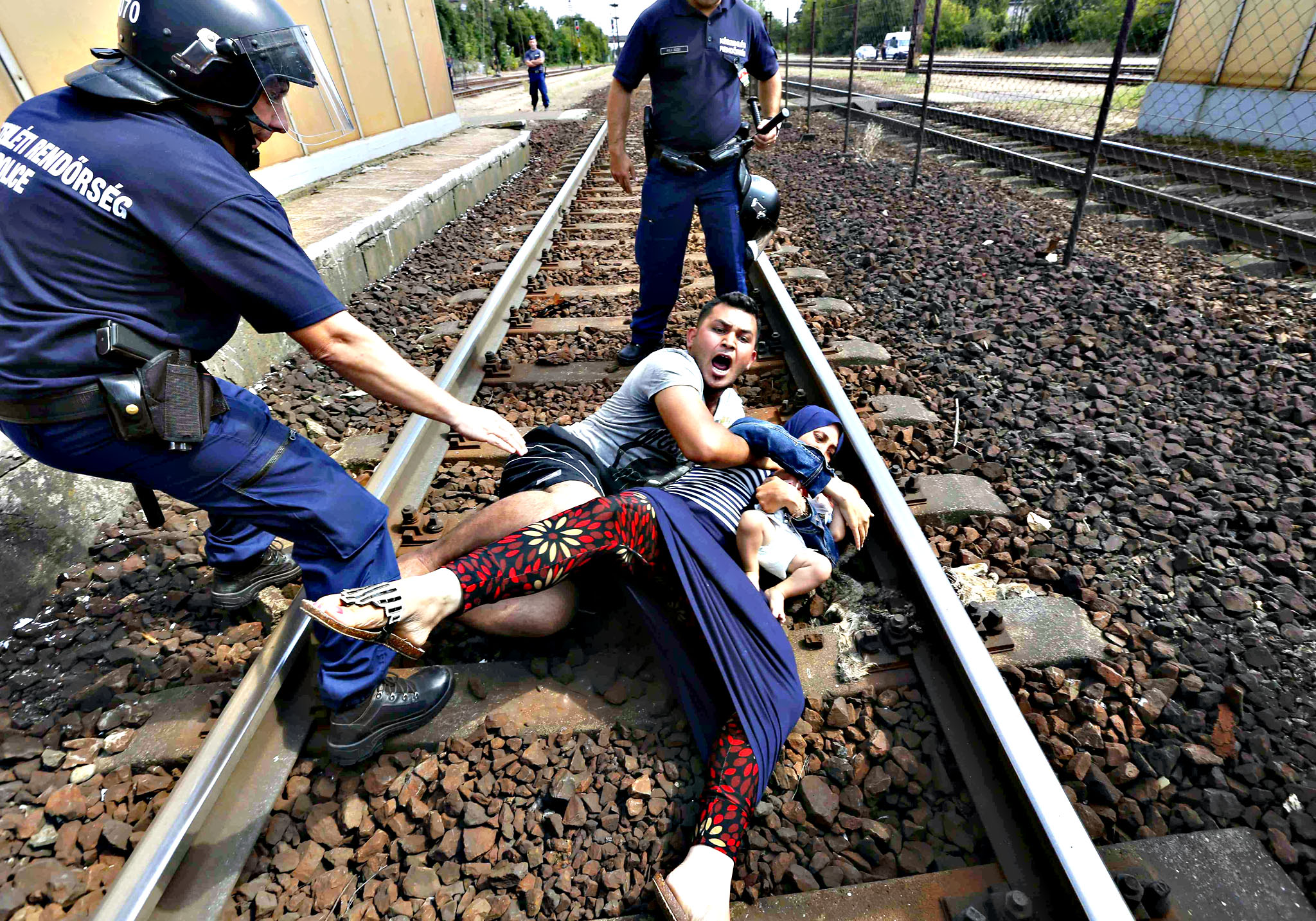 Hungarian policemen stand by the family of migrants protesting on the tracks at the railway station in the town of Bicske, Hungary on Thursday