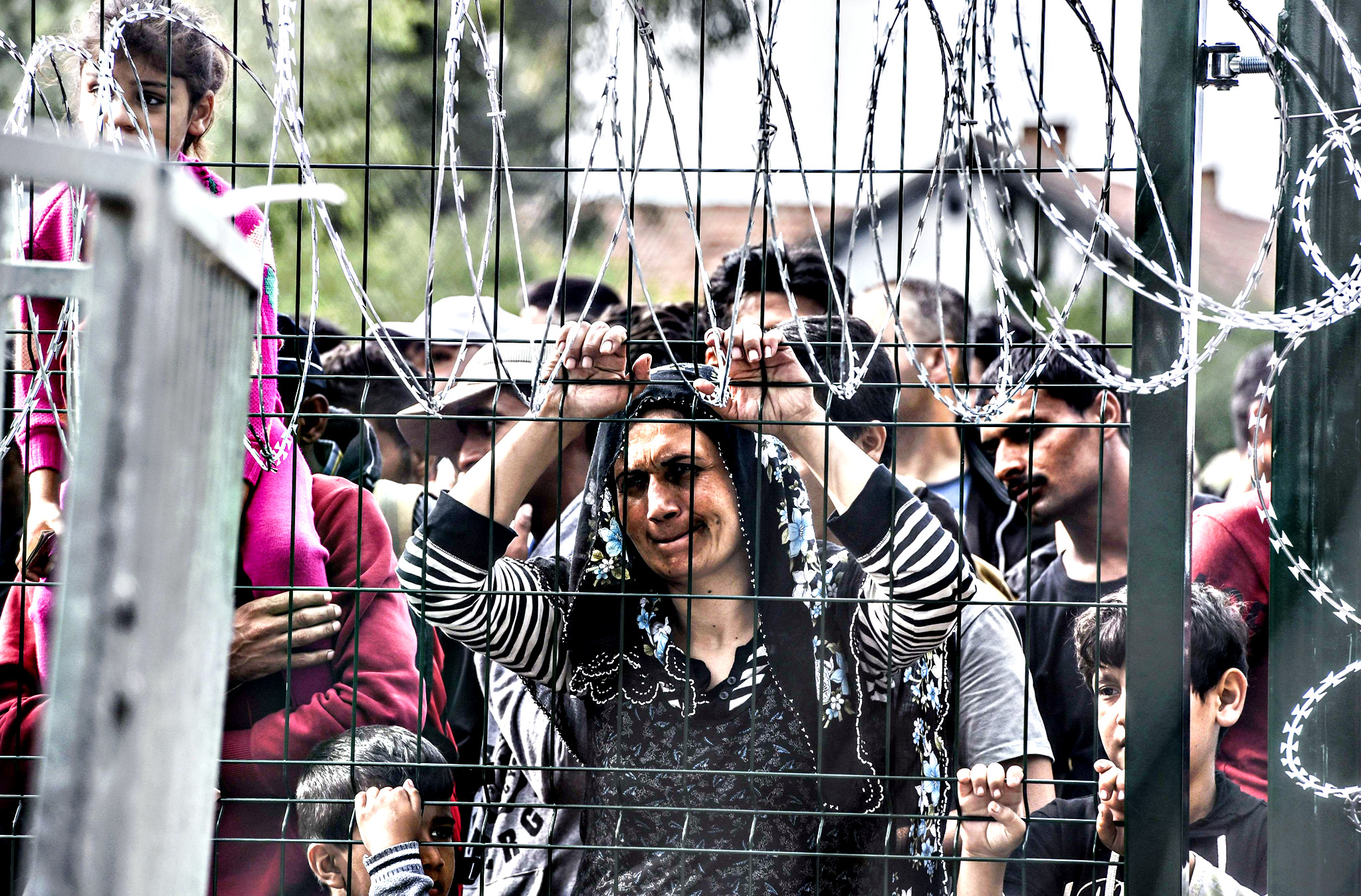 Hungarian border police stand guard opposite refugees standing behind a fence at the Hungarian border with Serbia near the town of Horgos on September 16, 2015. Europe's 20-year passport-free Schengen zone appeared to be a risk of crumbling with Germany boosting border controls on parts of its frontier with France as migrants desperate to find a way around Hungary's border fence began crossing into Croatia. With a string of EU countries tightened frontier controls in the face of the unprecedented human influx, the cherished principle of free movement across borders -- a pillar of the European project -- seemed in grave jeopardy