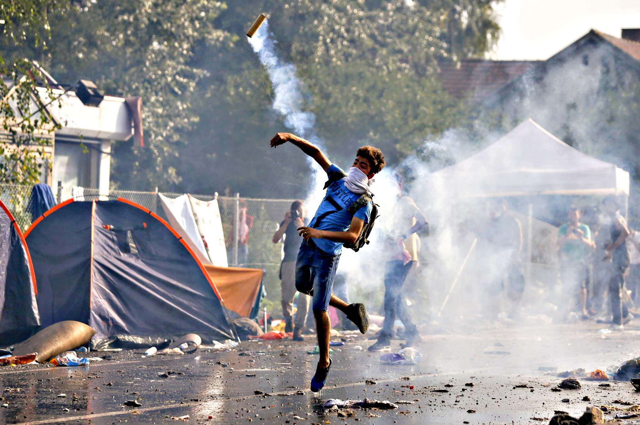 A migrant protests as Hungarian riot police fires tear gas and water cannon at the border crossing with Serbia in Roszke...A migrant protests as Hungarian riot police fires tear gas and water cannon at the border crossing with Serbia in Roszke, Hungary September 16, 2015. Hungarian police fired tear gas and water cannon at protesting migrants demanding they be allowed to enter from Serbia on Wednesday on the second day of a border crackdown