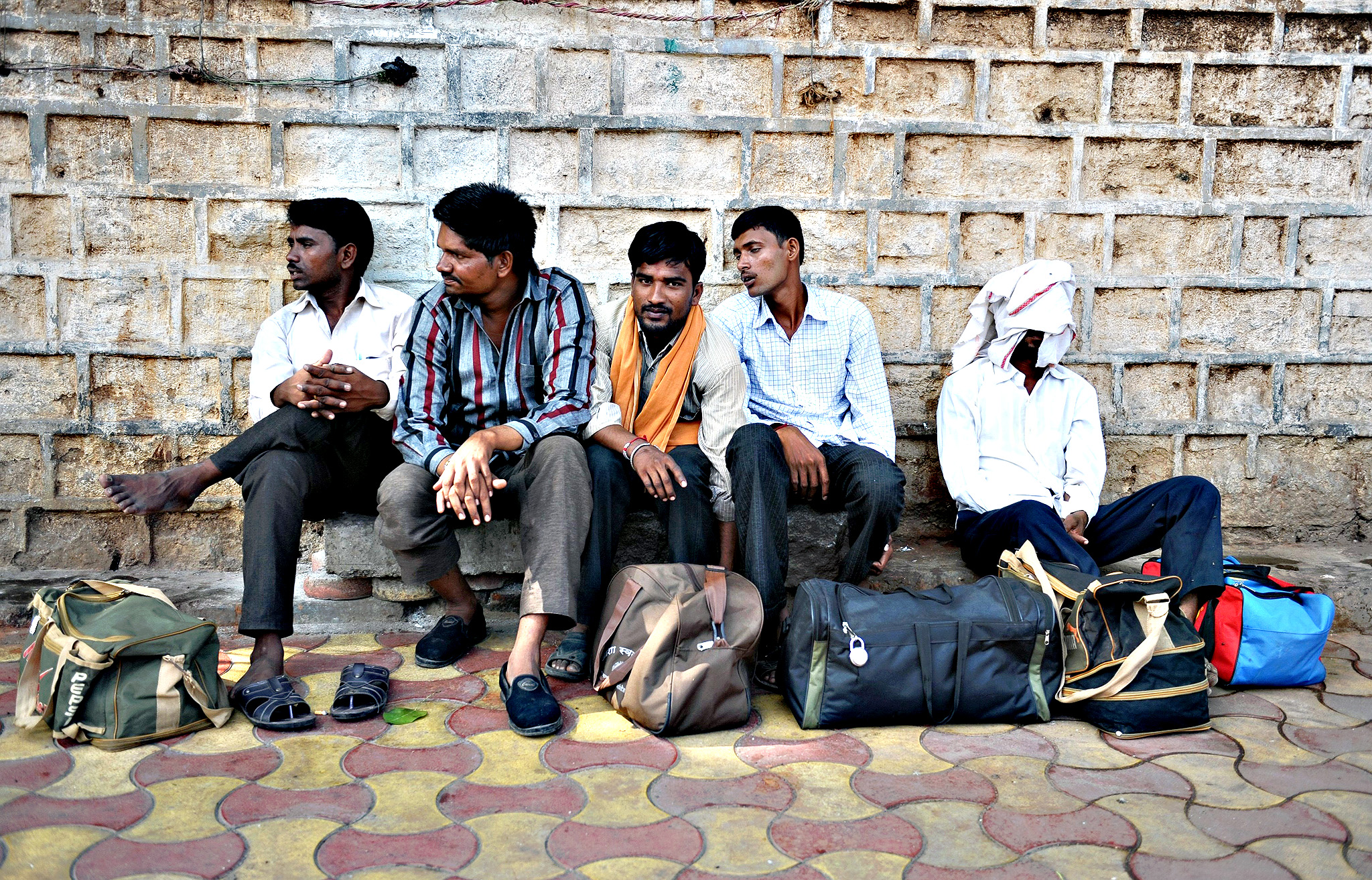Indian men wait for transport on the side of a road in Secunderabad, the twin city of Hyderabad, on Wednesday. Millions of workers across India held a 24-hour strike in protest at right-wing Prime Minister Narendra Modi's economic policies, which they say will put jobs at risk and hurt ordinary people.  Some 150 million workers, including those in the banking, manufacturing, construction and coal mining sectors, were expected to walk off the job