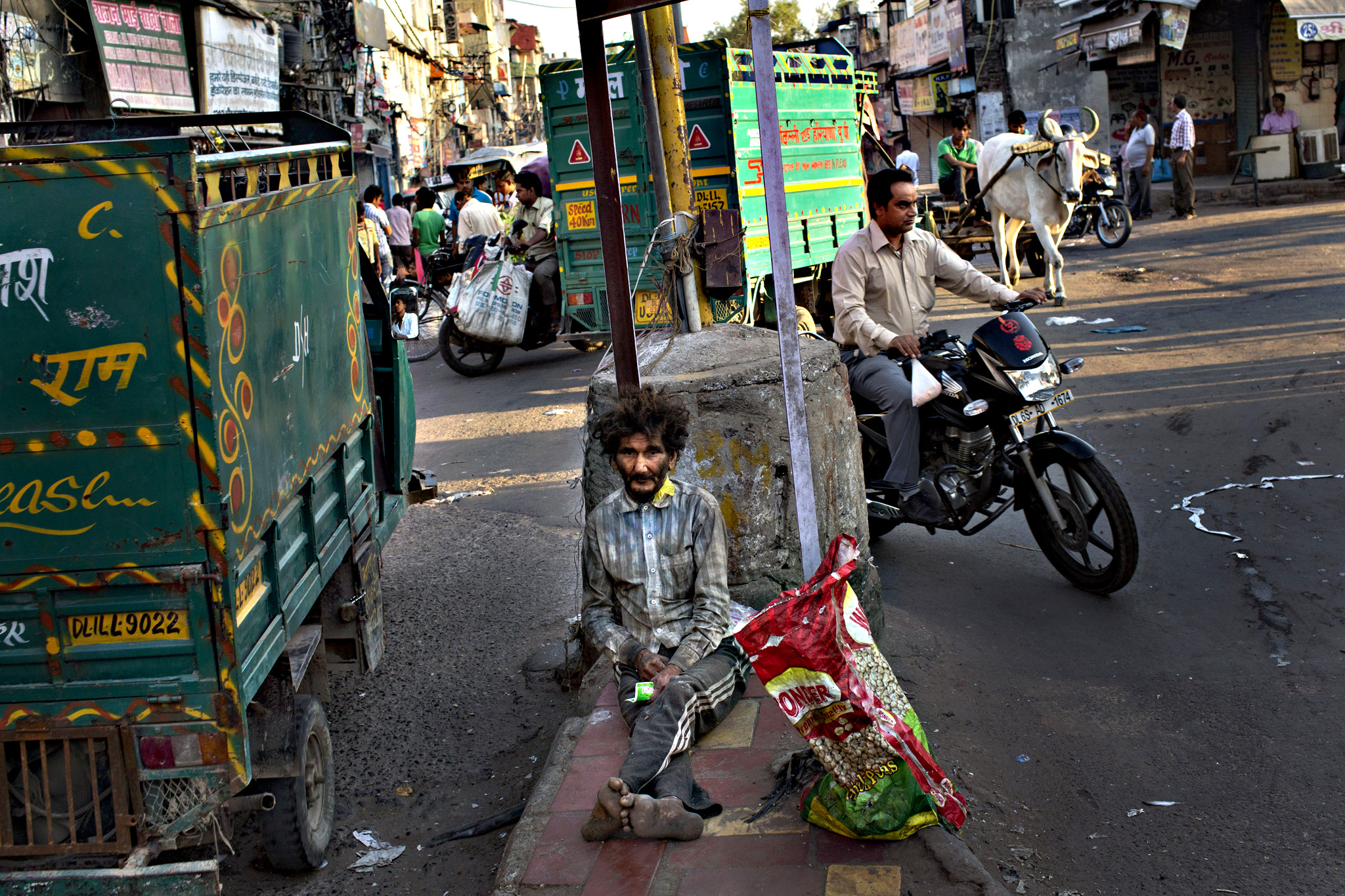 A homeless Indian man sits at a traffic intersection in the morning in New Delhi, India, Wednesday, Sept. 30, 2015. Hundreds of millions of Indians still live on less than $2 a day. The United Nations global goals for sustainable development in the next fifteen years, seeks to end poverty in all its forms everywhere