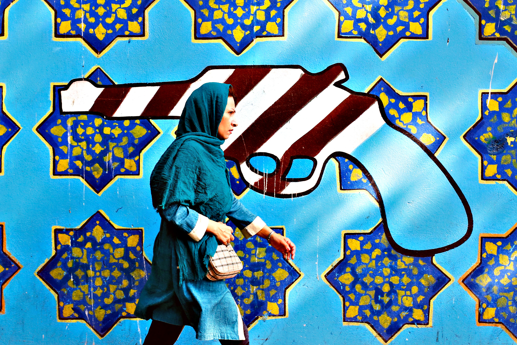 An Iranian woman walks past a painting of a revolver, painted in an American-flag style, on the wall of former US embassy in Tehran, Iran, on Wednesday. According to reports, a panel carrying some 100 anti-US comments by Iranian late supreme leader Ayatollah Ruhollah Khomini was placed on the wall of the former US embassy in Tehran. A group of Iranian students burnt American, British and Israeli flags rejecting restoring relations with the US after reaching the nuclear deal