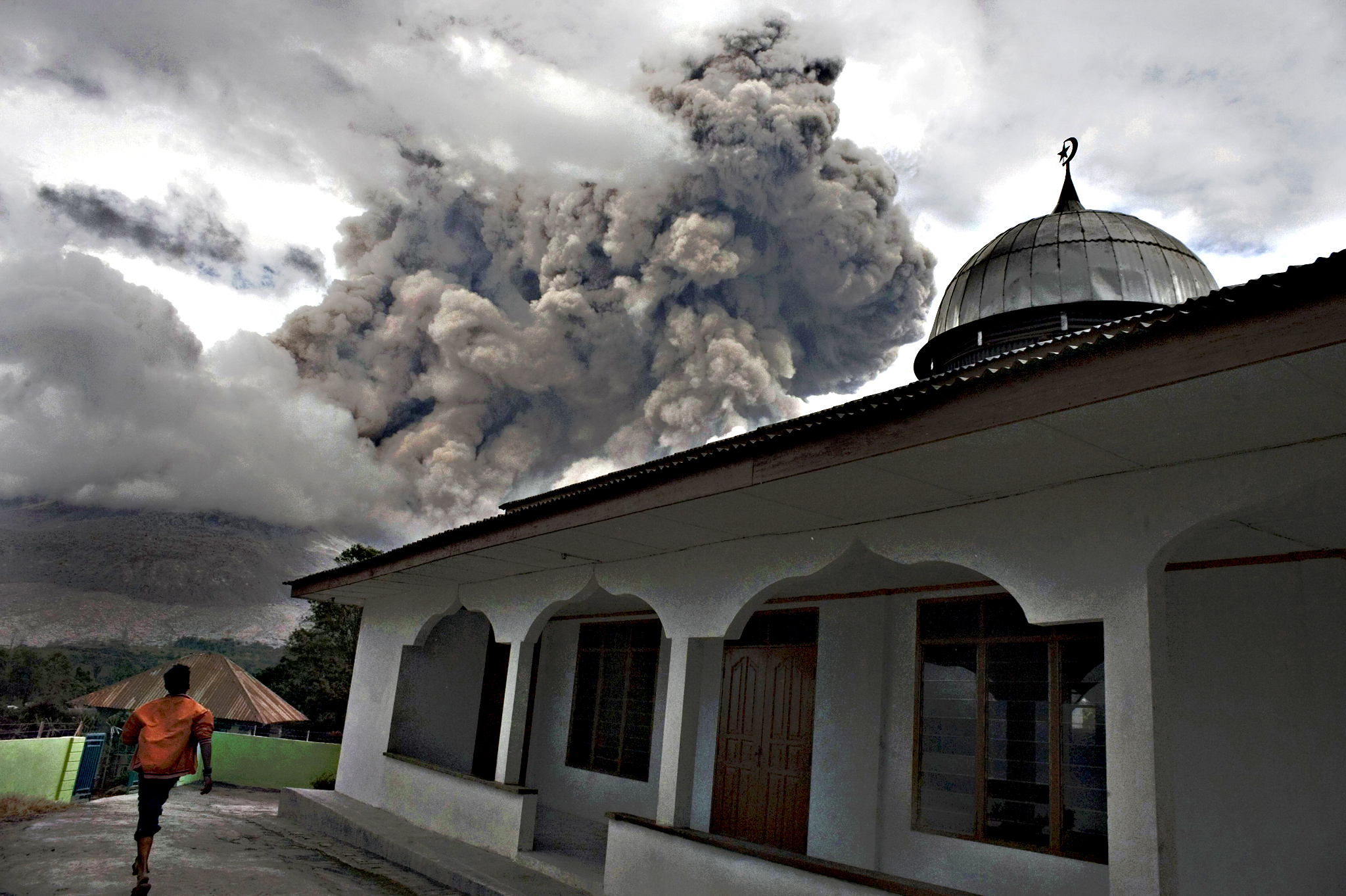 An Indonesian man stands next to a mosque in the village of Tiga Serangkai in Karo, North Sumatra on Wednesday, as mount Sinabung spews volcanic ash in the distance. Sinabung is one of 129 active volcanoes in Indonesia, which sits on the Pacific Ring of Fire, a belt of seismic activity running around the basin of the Pacific Ocean
