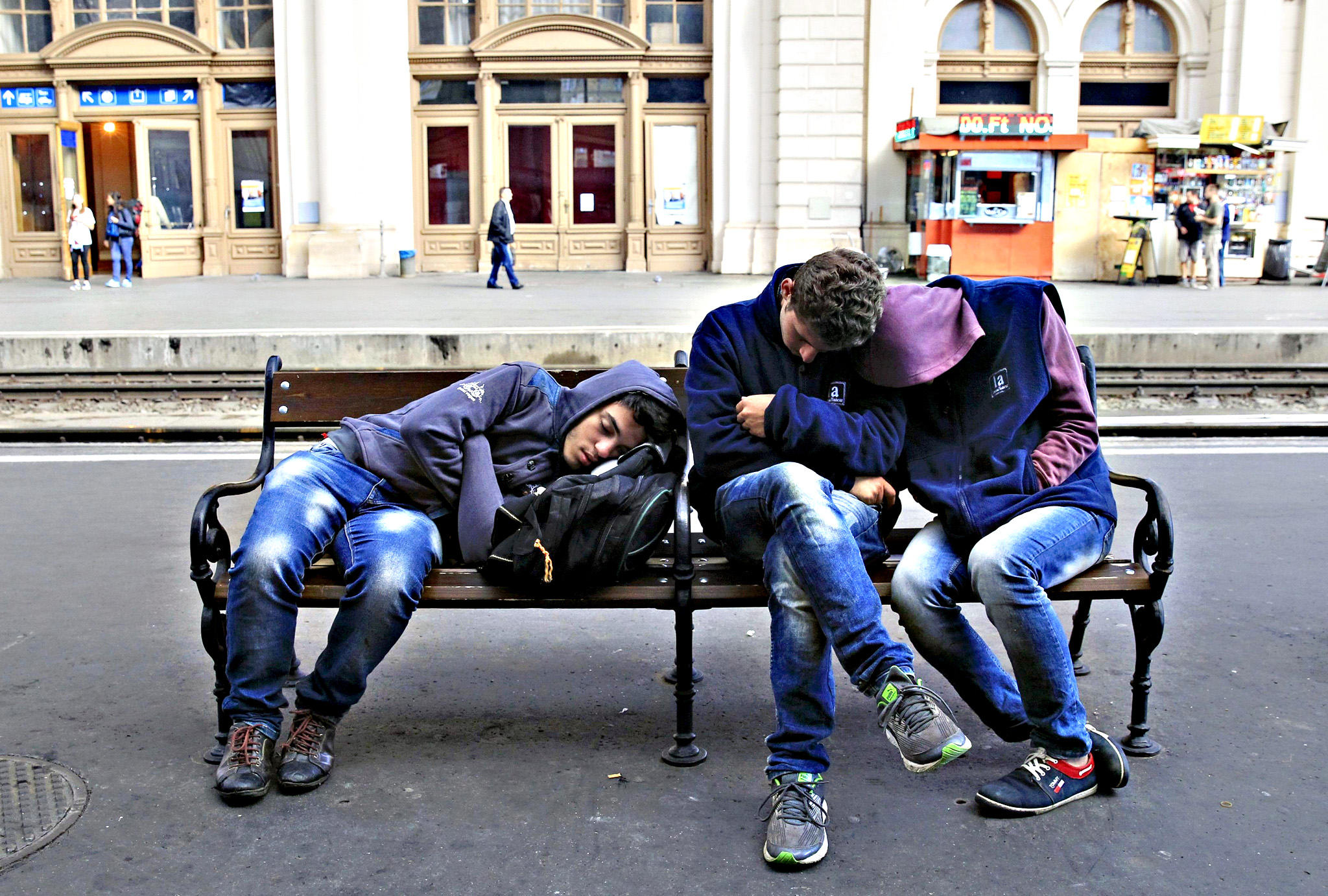 Migrants rest on a bench as they wait for trains at Keleti station in Budapest...Migrants rest on a bench as they wait for trains at Keleti station in Budapest, Hungary September 9, 2015
