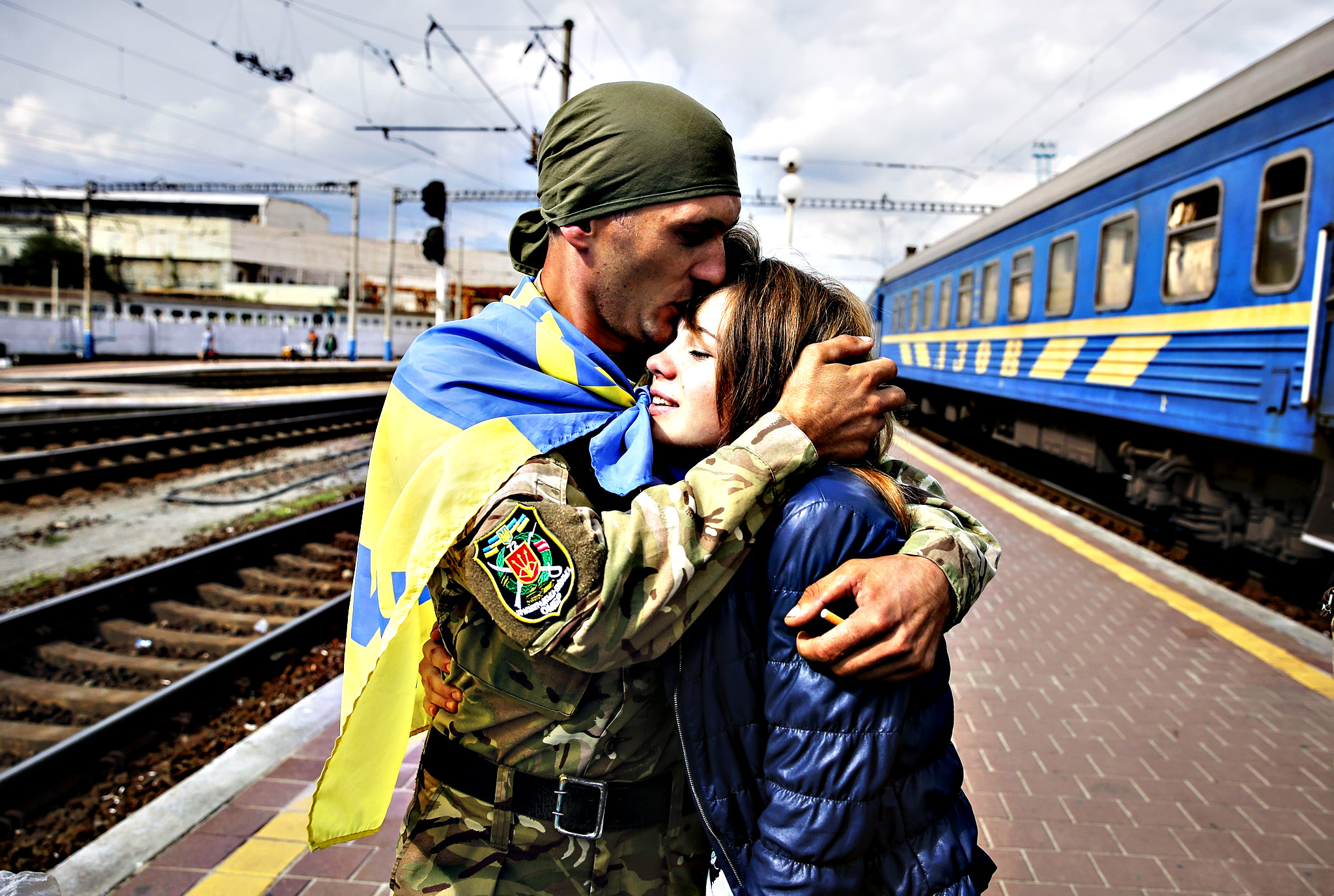 A discharged Ukrainian serviceman kisses his girlfriend on a platform of Kiev railway station as he arrived in the capital after one year fighting at the eastern-Ukrainian conflict zone 09 September 2015. Close to 8,000 civilians, Ukrainian soldiers and pro-Russian separatists have been killed in the conflict in eastern Ukraine since April last year, the UN human rights office said 8 September. The UN said the figures of at least 7,962 people killed and 17,811 wounded were conservative estimates, and the actual numbers could be far higher