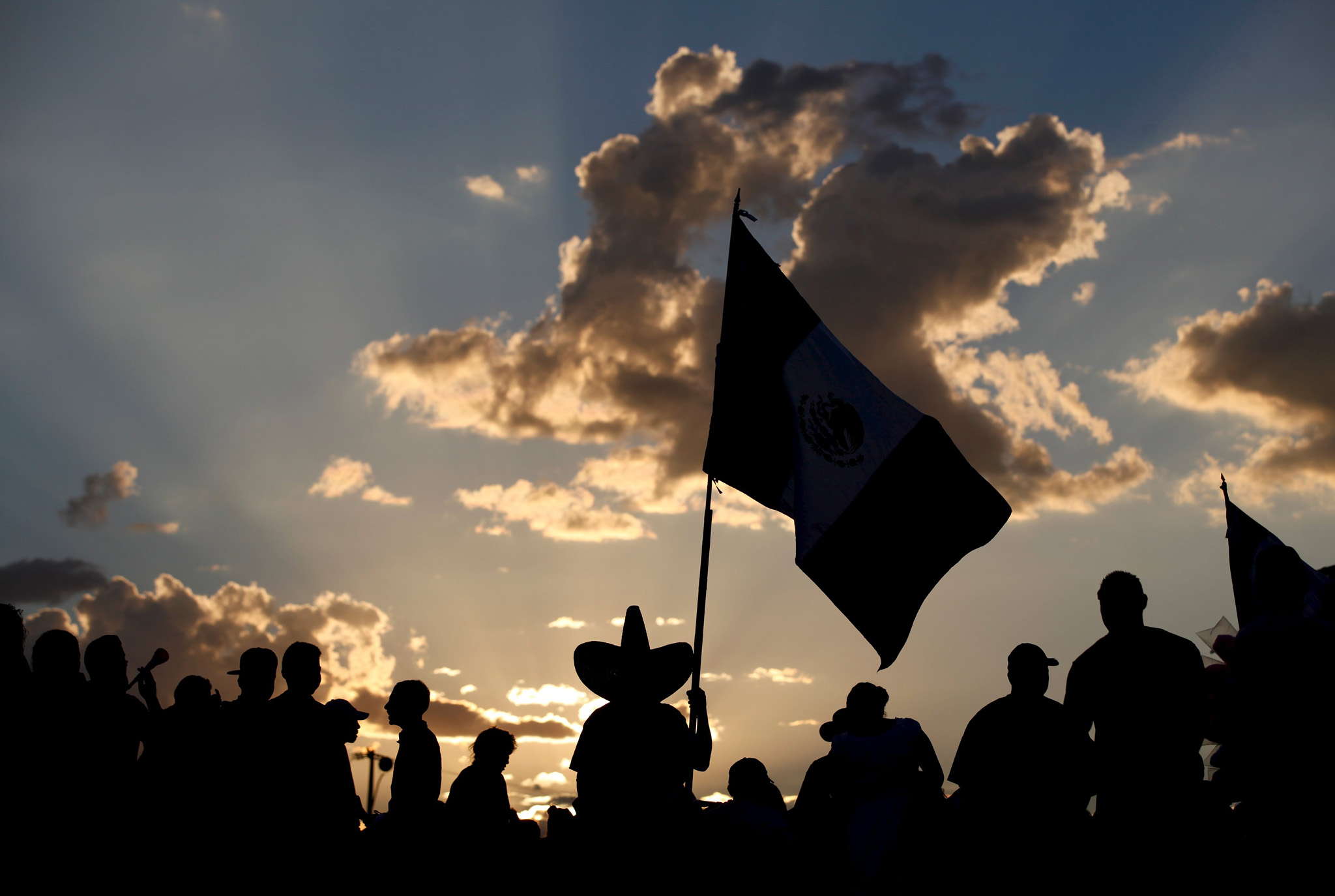 "Man carrying a Mexican flag is silhouetted while attending the ""Cry of Independence"""