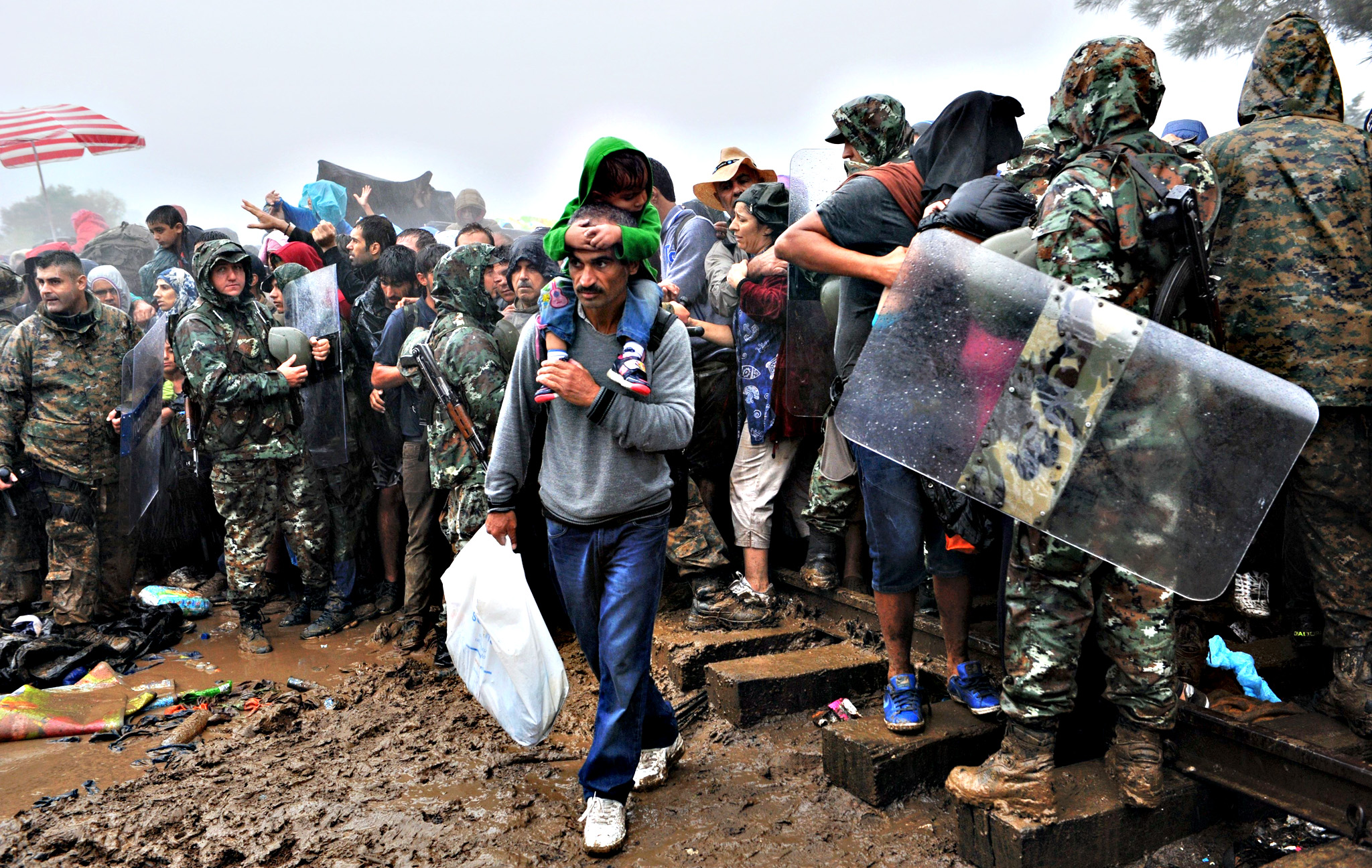 Migrants and refugees wait under the rain to cross the Greek-Macedonian border near the village of Idomeni, in northern Greece onThursday. More than 10 thousands refugees and migrants arrived in Piraeus from the overcrowded Greek islands, especially the island of Lesbos , in the last 24 hours