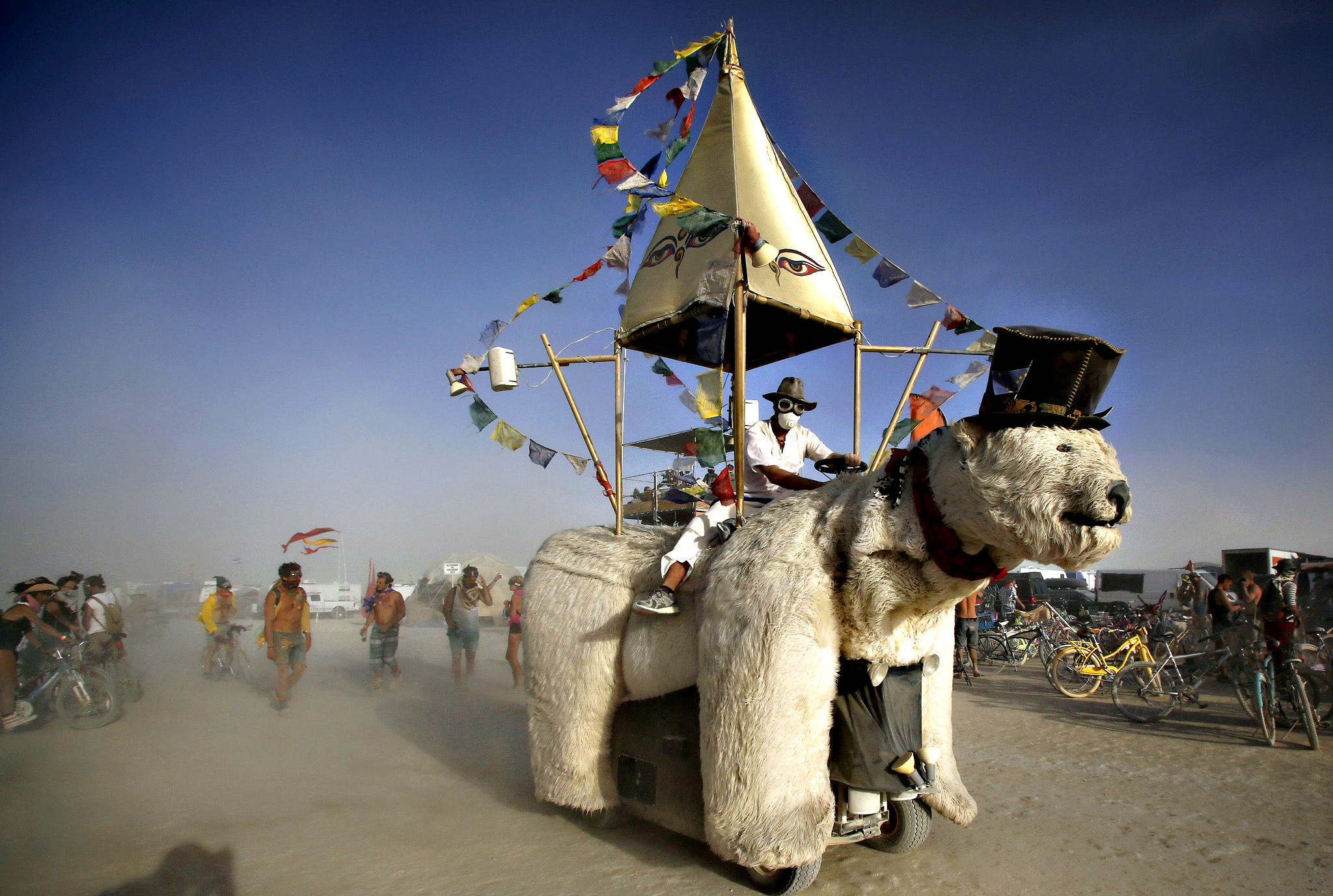 "A Mutant Vehicle made up like a polar bear drives through the dust during the Burning Man 2015 ""Carnival of Mirrors"" arts and music festival in the Black Rock Desert of Nevada. Participants from all over the world attend the sold-out festival to spend a week in the remote desert to experience art, music and the unique community that develops"
