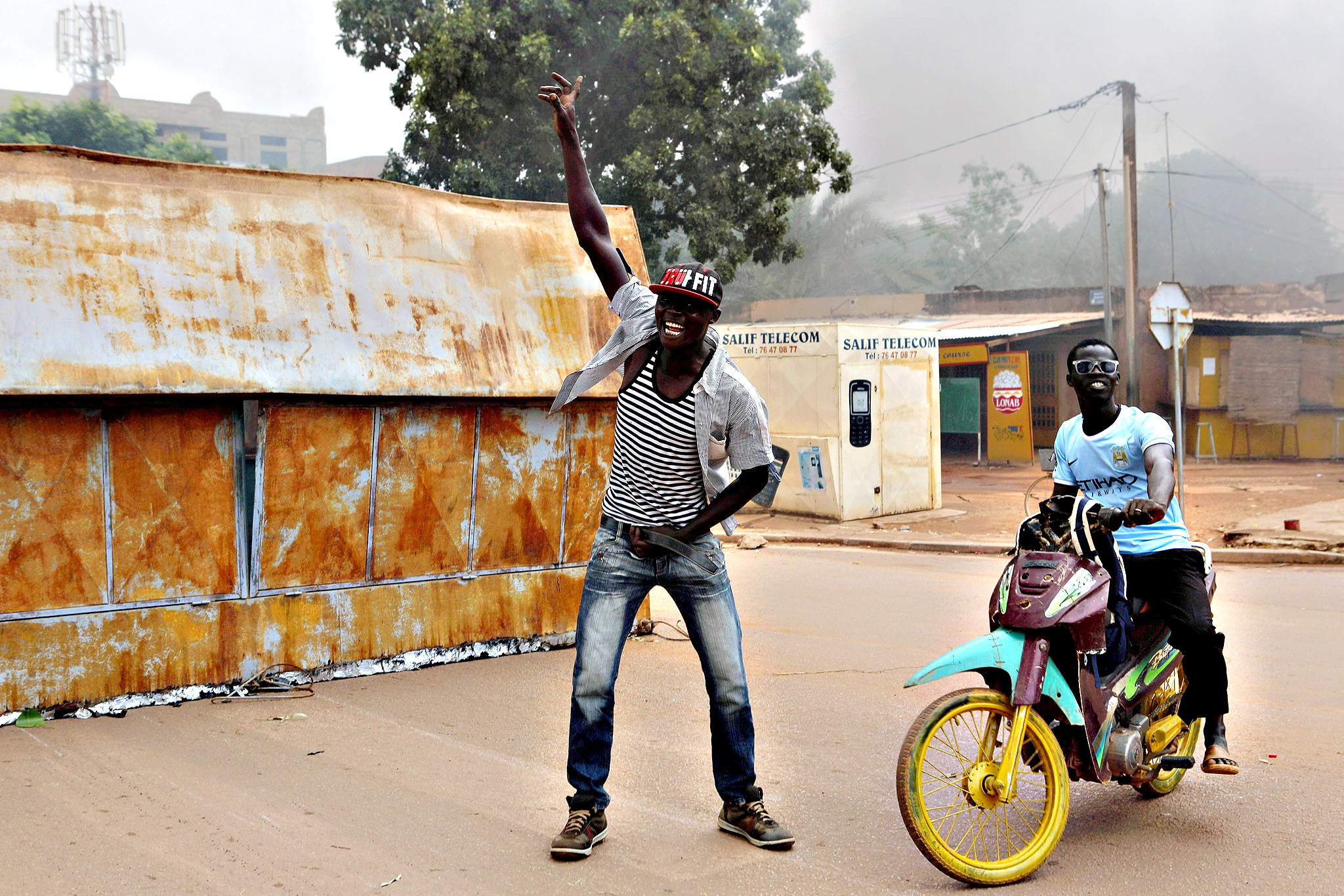 A protester raises his fist in Ouagadougou, Burkina Faso, September 18, 2015. Security forces in the capital of Burkina Faso fired in the air on Friday to disperse demonstrators who burned tyres and blocked neighborhood streets to protest at a military coup this week that derailed a democratic transition. The head of a military junta in Burkina Faso which took power on Thursday has freed interim President Michel Kafando and two of his ministers, state television said on Friday