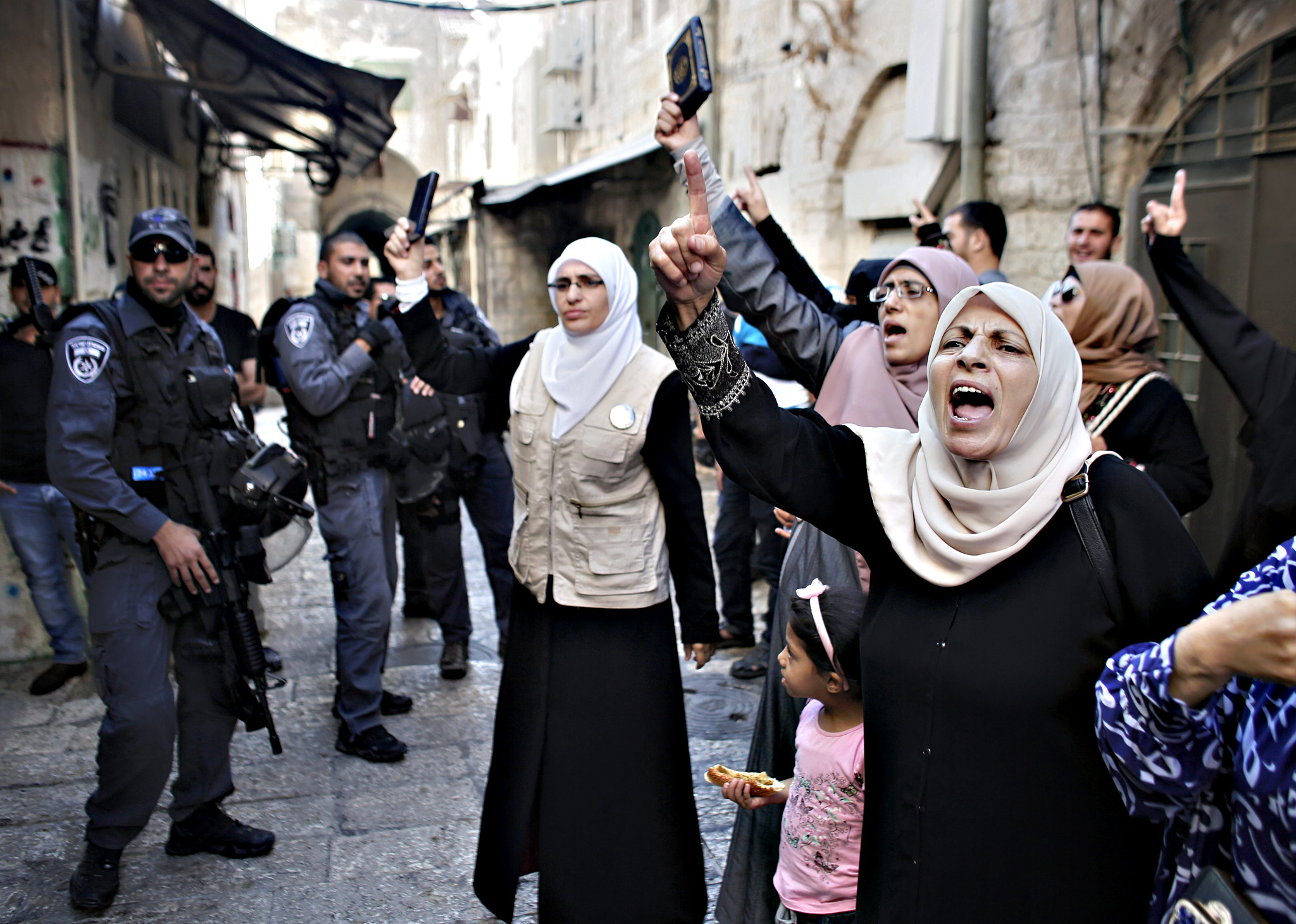 Palestinian women from the so-called Murrabit group raise copies of the Koran, Islam's holy book, and shout slogans in front of Israeli security forces during a protest against Jewish groups visiting the Al-Aqsa mosque compound in Jerusalems old city on September 22, 2015. Israel said thousands of police would be deployed in Jerusalem ahead of the Yom Kippur and Eid al-Adha holidays after three days of clashes rocked the Al-Aqsa mosque compound.