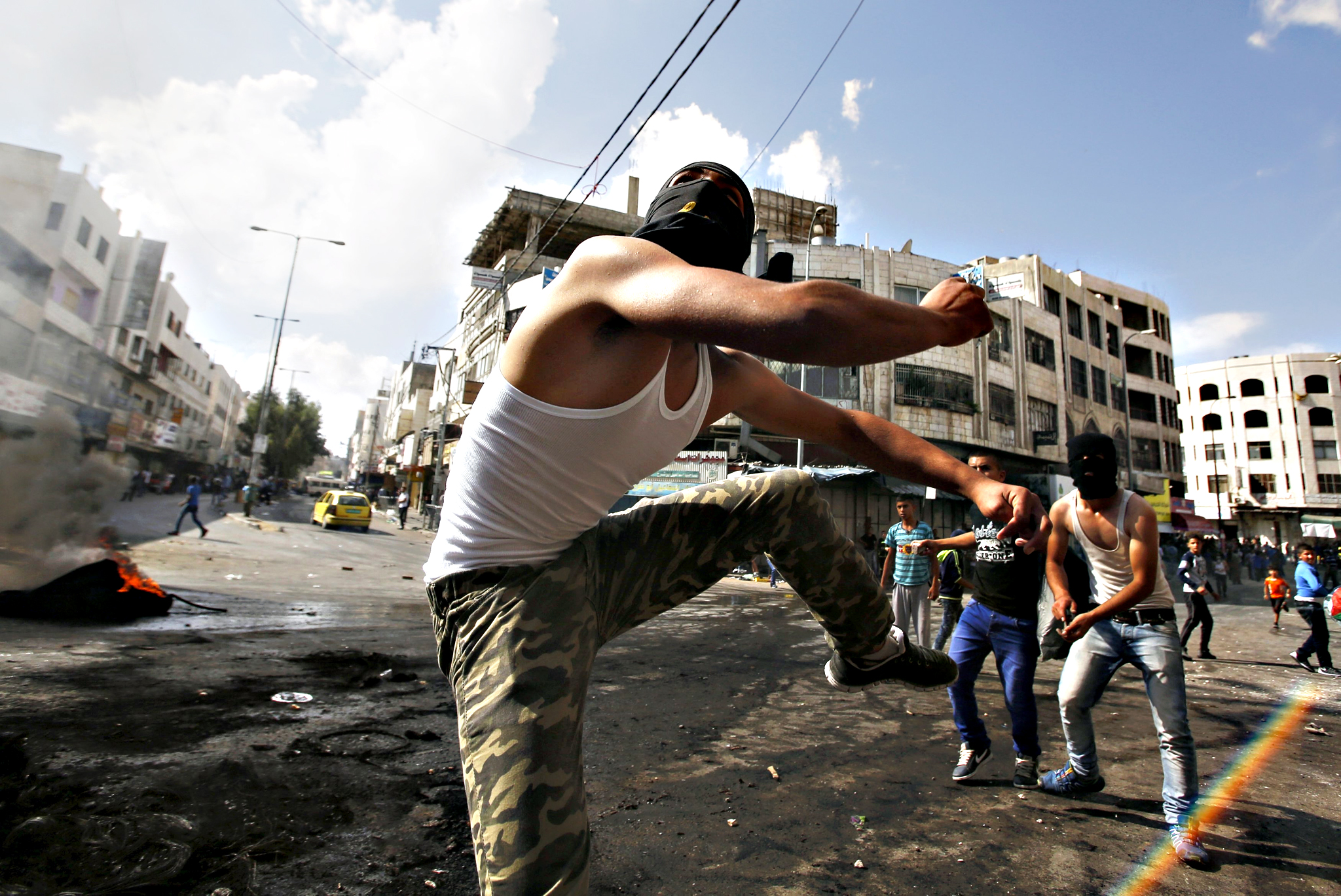 Palestinian protesters throw stones at Israeli troops during clashes over tension in Jerusalem's al-Aqsa mosque, in the occupied West Bank city of Hebron...Palestinian protesters throw stones at Israeli troops during clashes over tension in Jerusalem's al-Aqsa mosque, in the occupied West Bank city of Hebron September 29, 2015. Israeli police and Palestinians clashed on Sunday at Jerusalem's al-Aqsa mosque compound, where violence in recent weeks has raised international concern.