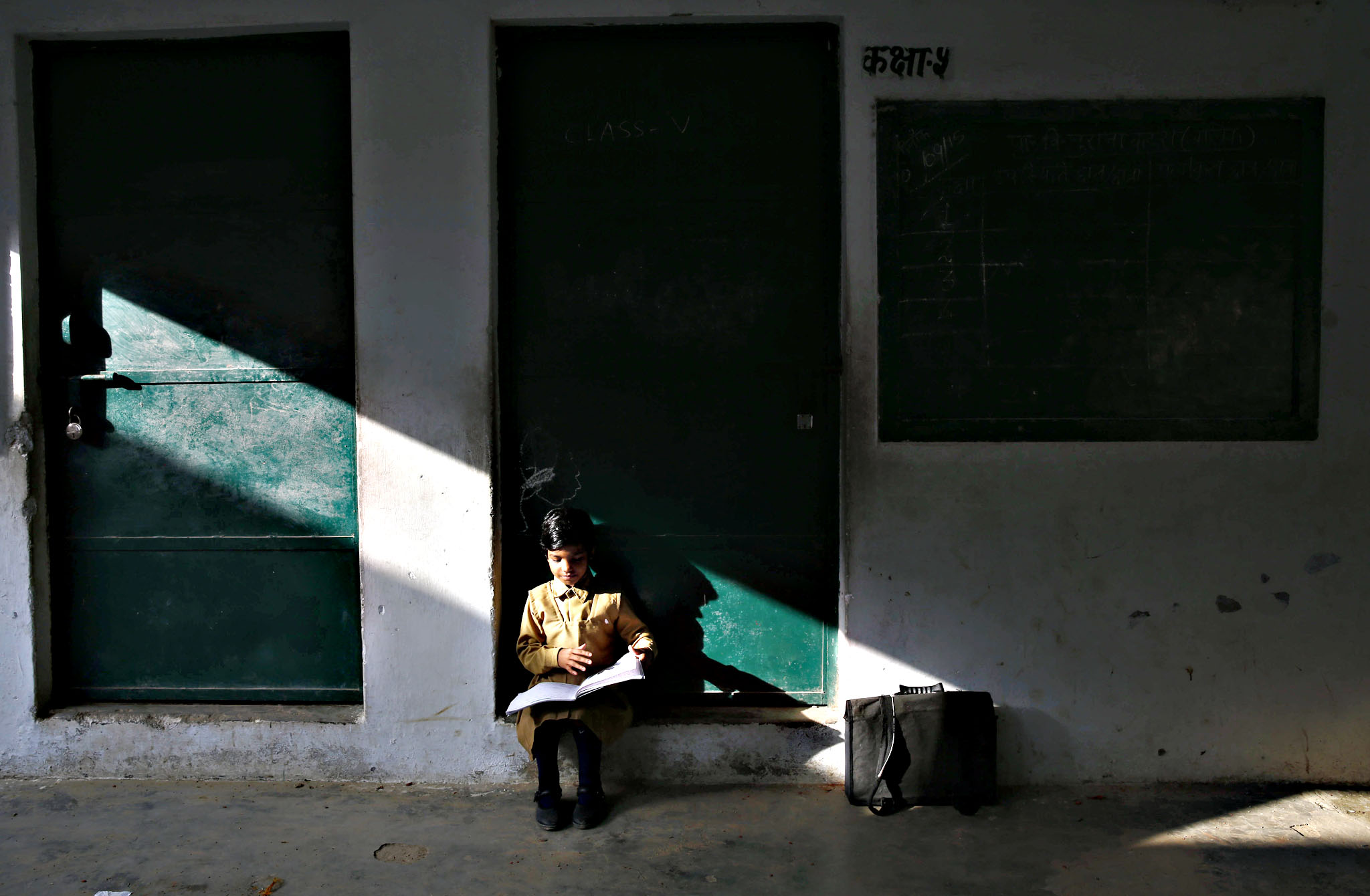 A child goes through his school book at a government-run school on the eve of International Literacy Day in Allahabad, India, Monday, Sept. 7, 2015. According to Indian Census 2011, the literacy rate is 74.04 percent of the total population aged seven and above, though the government has made a law that every child under the age of 14 should get free education, the problem of illiteracy is still at large especially in the rural areas