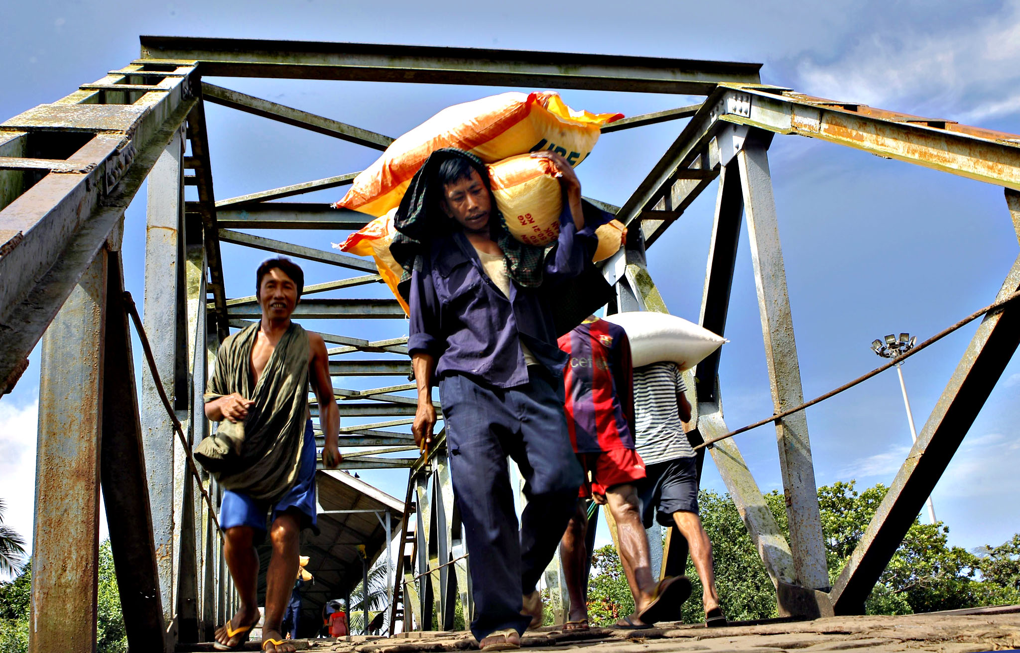 Myanmar worker carries rice bags on his shoulder at a jetty near Yangon river, Yangon, Myanmar, 03 September 2015. Myanmar Rice Federation (MRF) official told media that Myanmar would resume rice export on mid-september which has halted since the first week of August after mooson heavy rain and floods hit around the nation. MRF said this year rice export is expected less than 1.5 millon tons despide the government firstly expected about 2 million tons of this fical year as about 400.000 hectares of rice fields were expected to be damaged by floods
