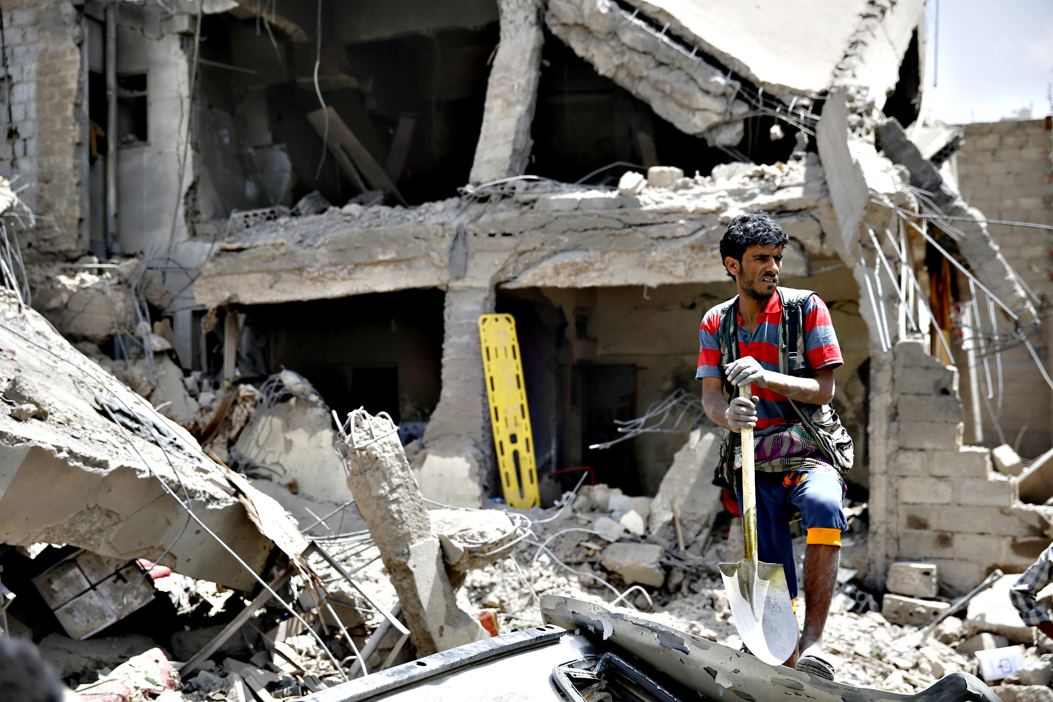 A man stands amid the rubble of houses destroyed in a Saudi-led airstrike in Sanaa, Yemen, Monday, Sept. 21, 2015.