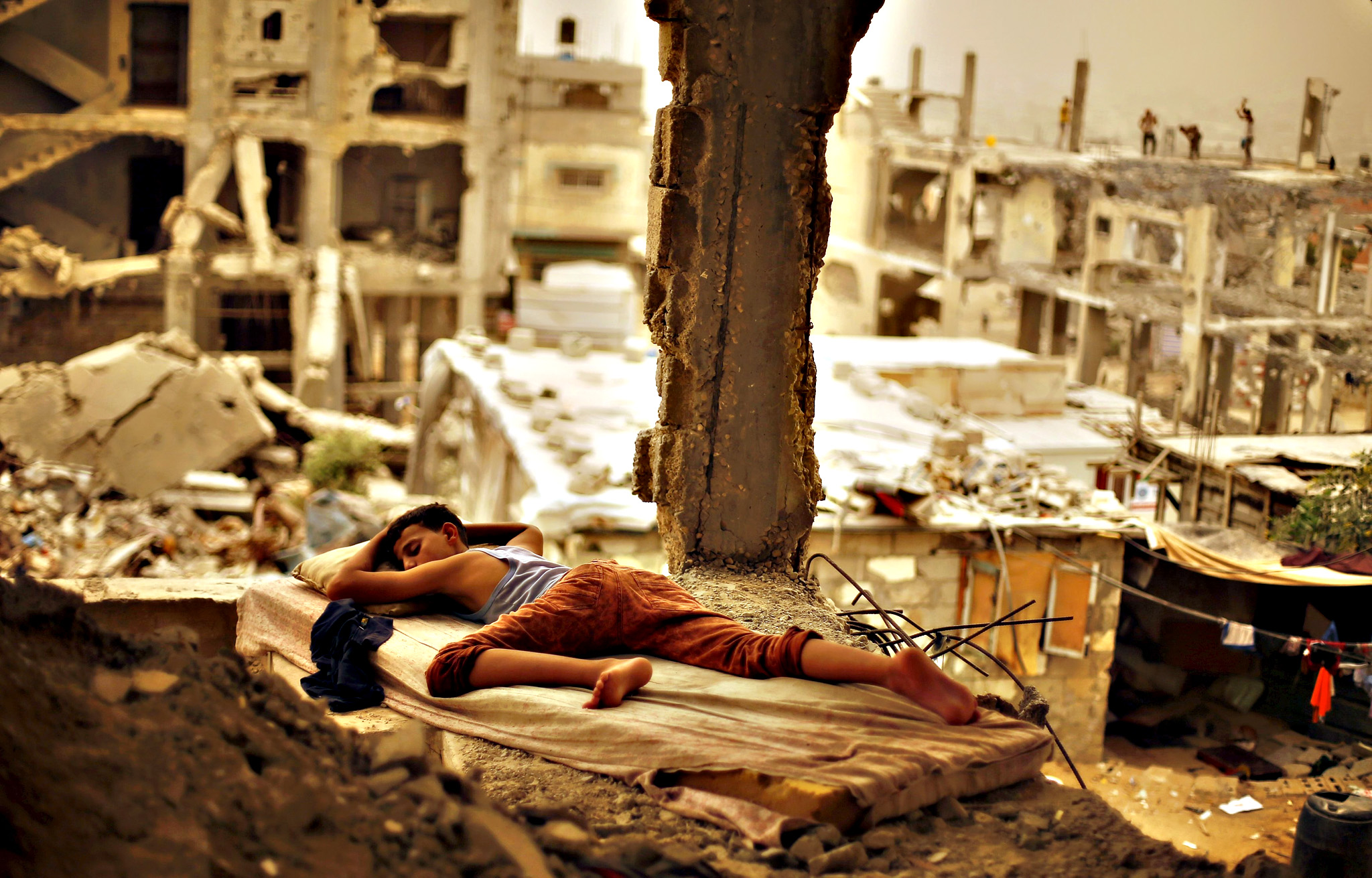 A Palestinian boy sleeps on a mattress inside the remains of his family's house, that witnesses said was destroyed by Israeli shelling during a 50-day war in 2014 summer, during a sandstorm in Gaza September 8, 2015. A heavy sandstorm swept across parts of the Middle East on Tuesday, killing two people and hospitalising hundreds in Lebanon and disrupting fighting and air strikes in neighbouring Syria. Clouds of dust also engulfed Israel, Jordan and Cyprus where aircraft were diverted to Paphos from Larnaca airport as visibility fell to 500 metres