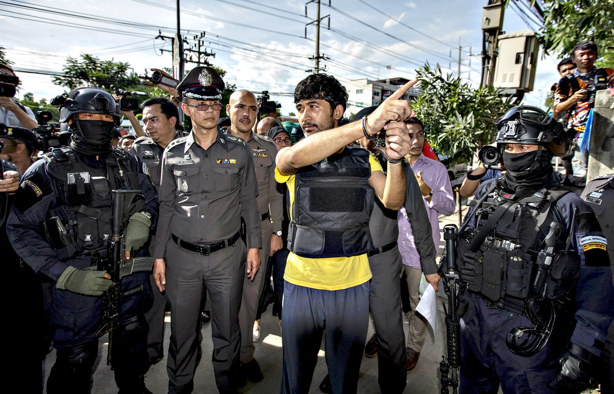 A suspect of the Aug. 17 Bangkok blast who was arrested last week near the border with Cambodia points as he stands next to police officers during a crime re-enactment at an apartment, where police raided and found possible bomb-making materials last month, in Nongjok district, on the outskirts of Bangkok, Thailand, September 8, 2015