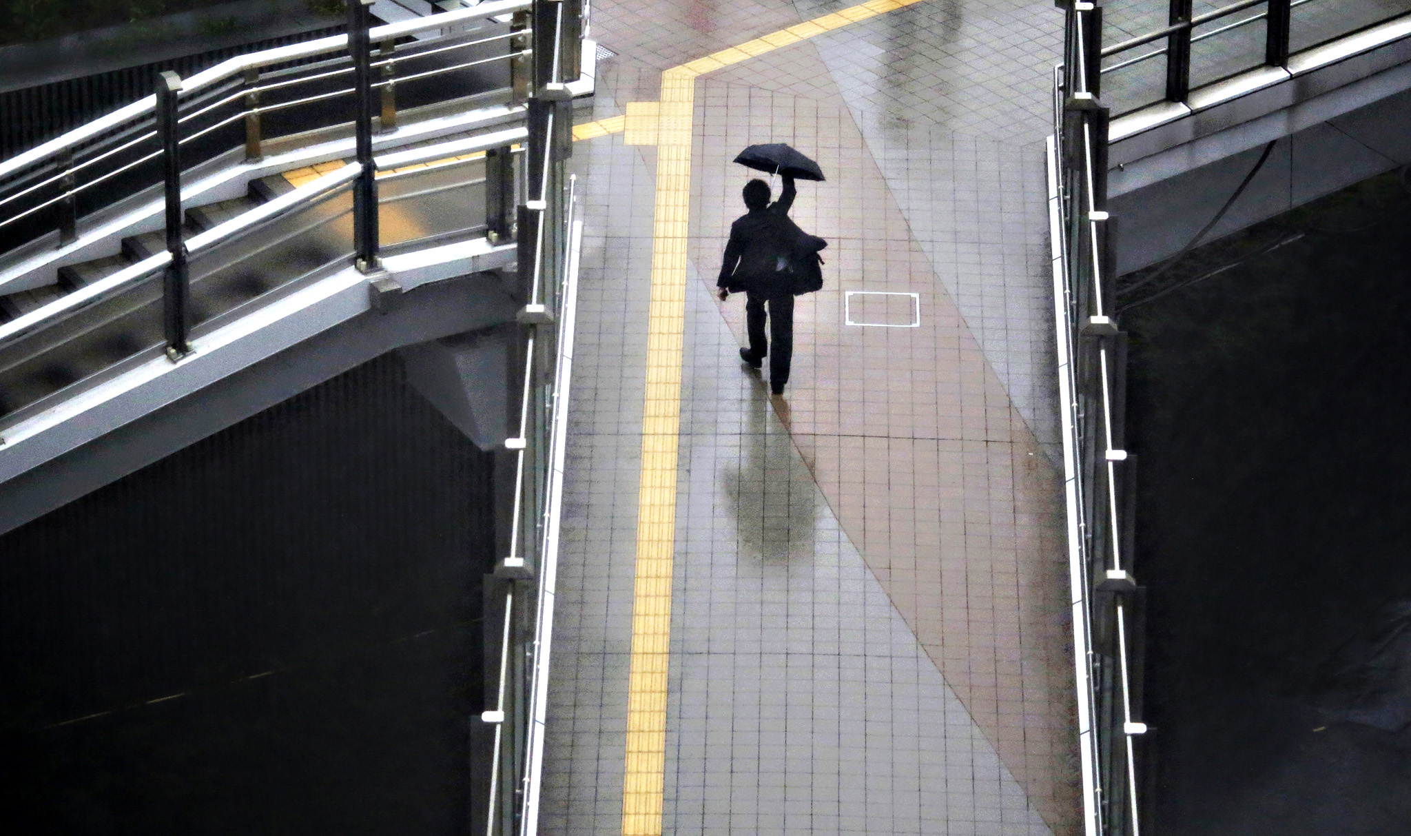 A man struggles to hold an umbrella in heavy rain at a business district in Tokyo Wednesday, Sept. 9, 2015. Heavy rain caused by a typhoon passing through central Japan hit the Tokyo metropolitan area in the day