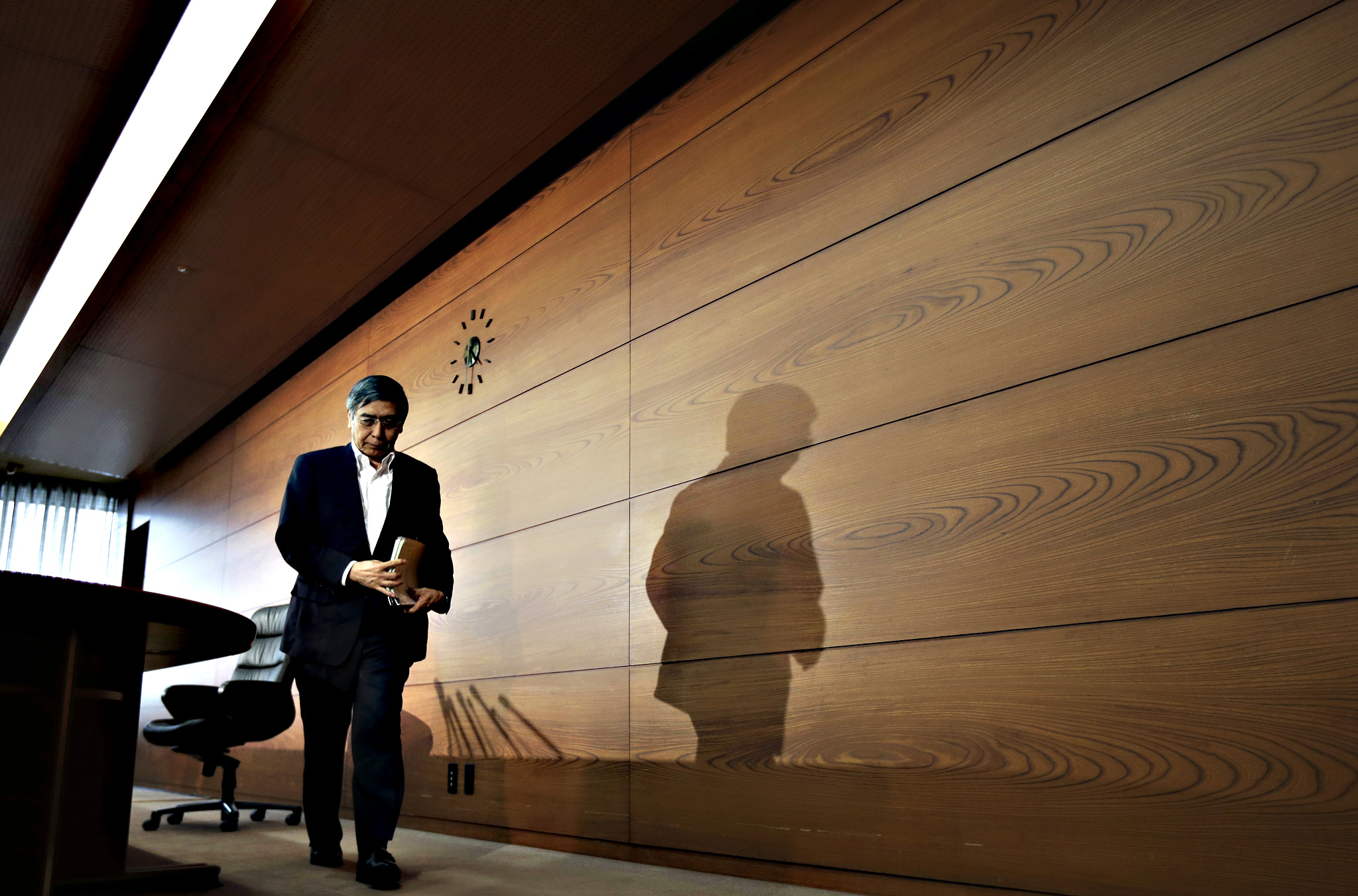 Bank Of Japan Governor Haruhiko Kuroda News Conference...Haruhiko Kuroda, governor of the Bank of Japan (BOJ), leaves a news conference at the central bank's headquarters in Tokyo, Japan, on Tuesday, Sept. 15, 2015. The BOJ refrained from boosting stimulus even after the economy shrank last quarter, betting that a resumption in growth will be enough to rekindle inflation