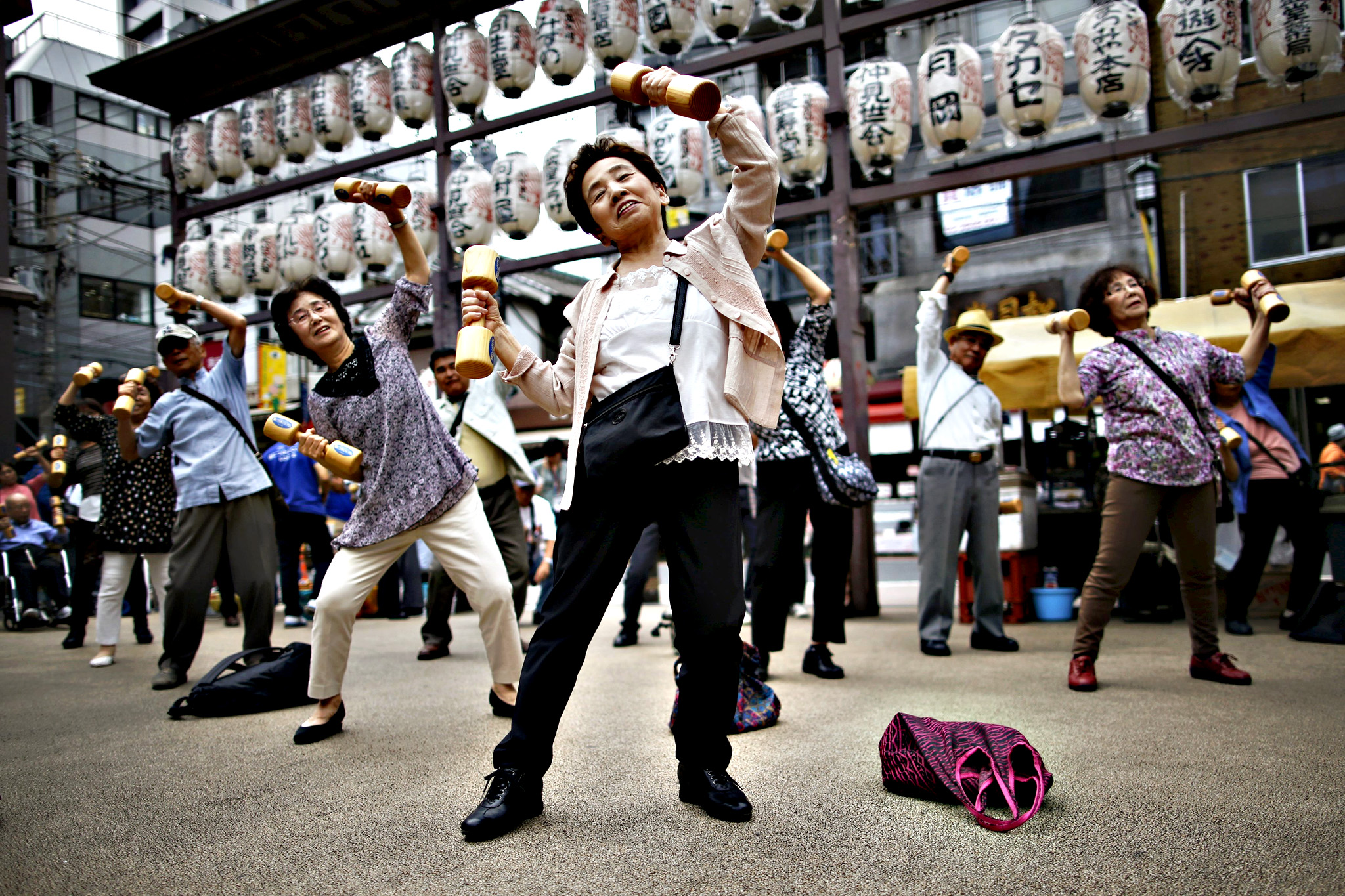 "Elderly and middle-age people exercise with wooden dumbbells during a health promotion event to mark Japan's ""Respect for the Aged Day"" at a temple in Tokyo...Elderly and middle-age people exercise with wooden dumbbells during a health promotion event to mark Japan's ""Respect for the Aged Day"" at a temple in Tokyo's Sugamo district, an area popular among the Japanese elderly, September 21, 2015."