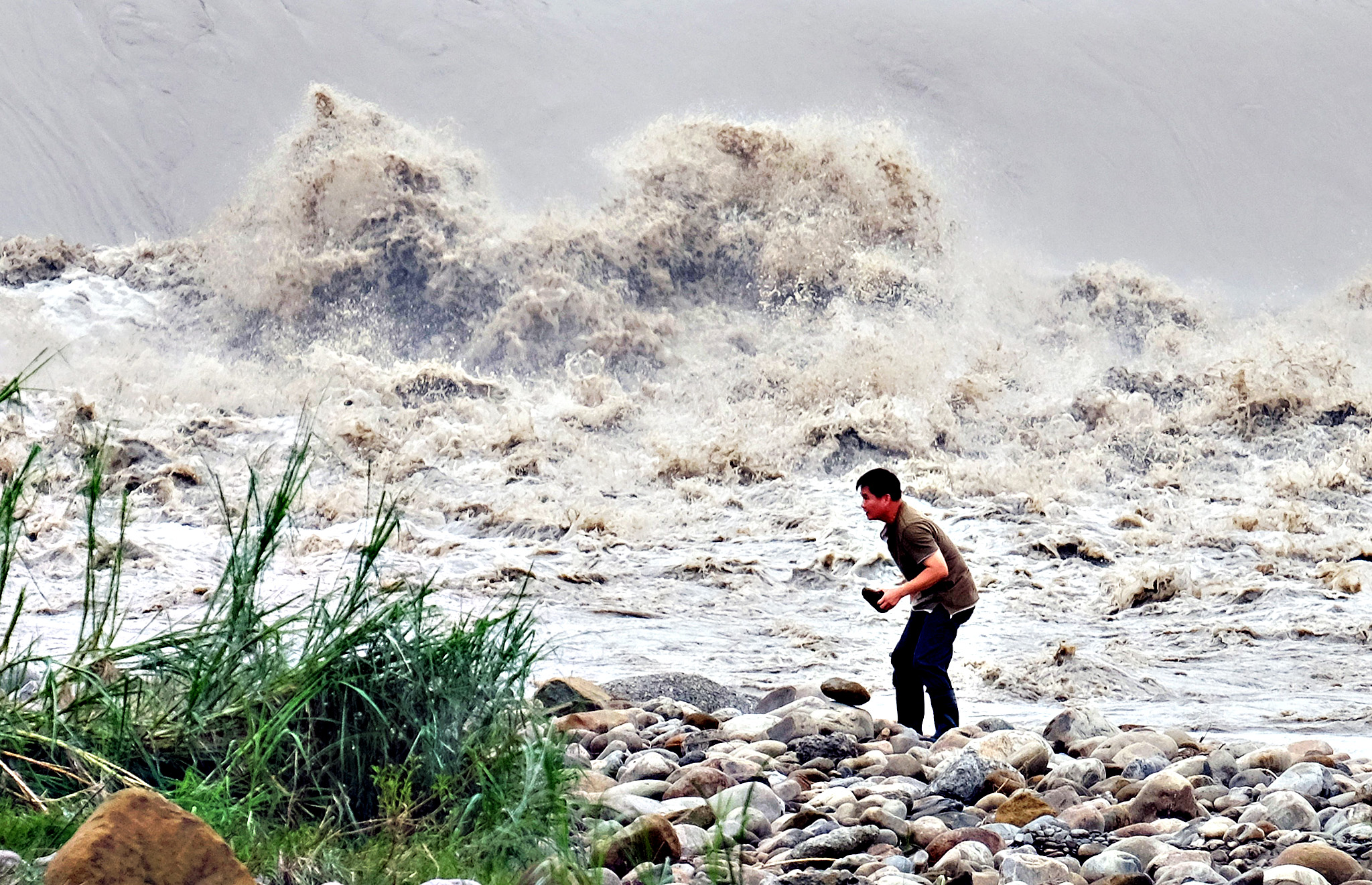 A local resident collects stones from the Xindian river after Typhoon Dujuan passed in the New Taipei City on September 29, 2015. Super typhoon Dujuan killed two and left more than 300 injured in Taiwan before making landfall in China.