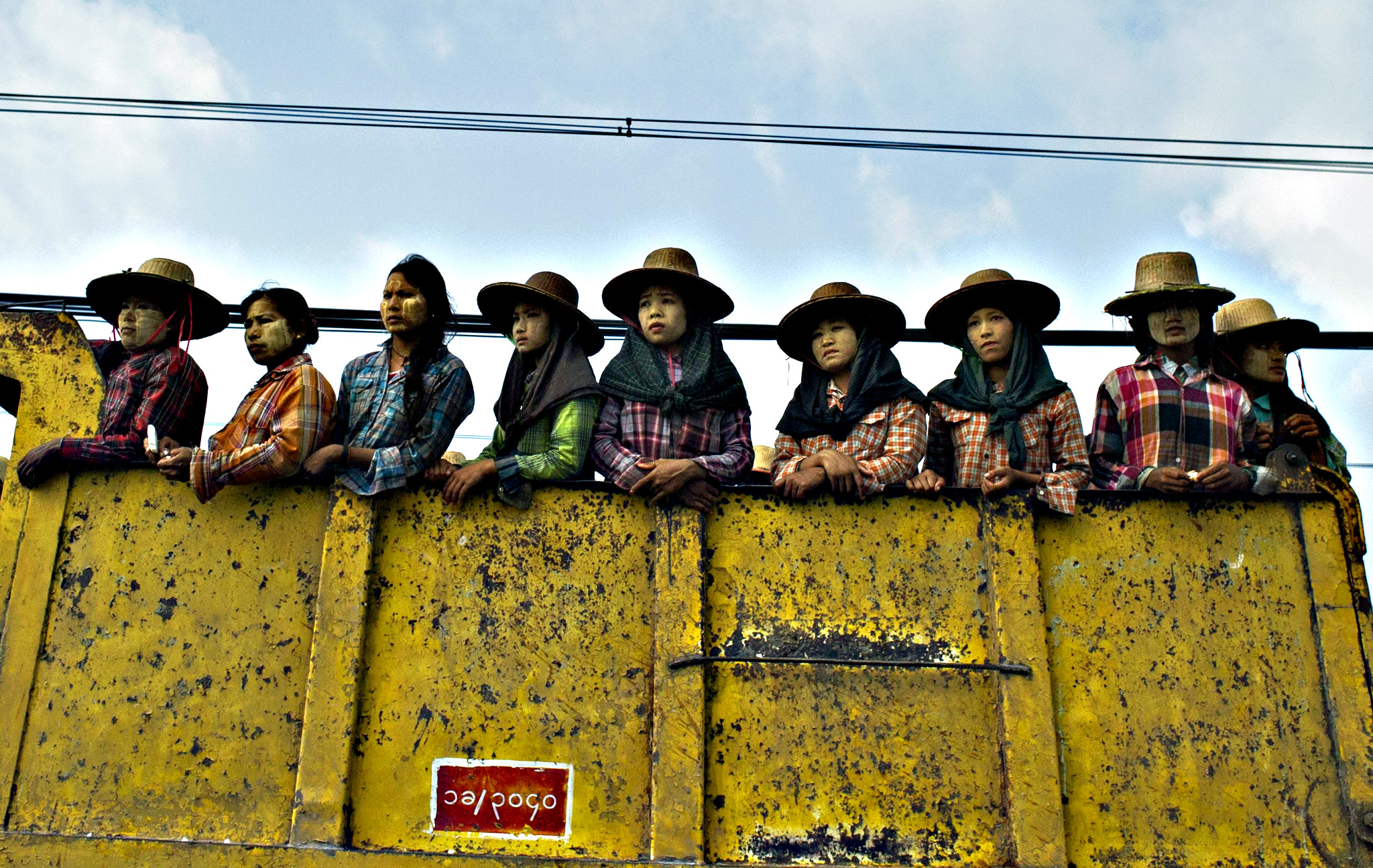 Labourers ride on truck on their way to work on the outskirt of Yangon on Monday.