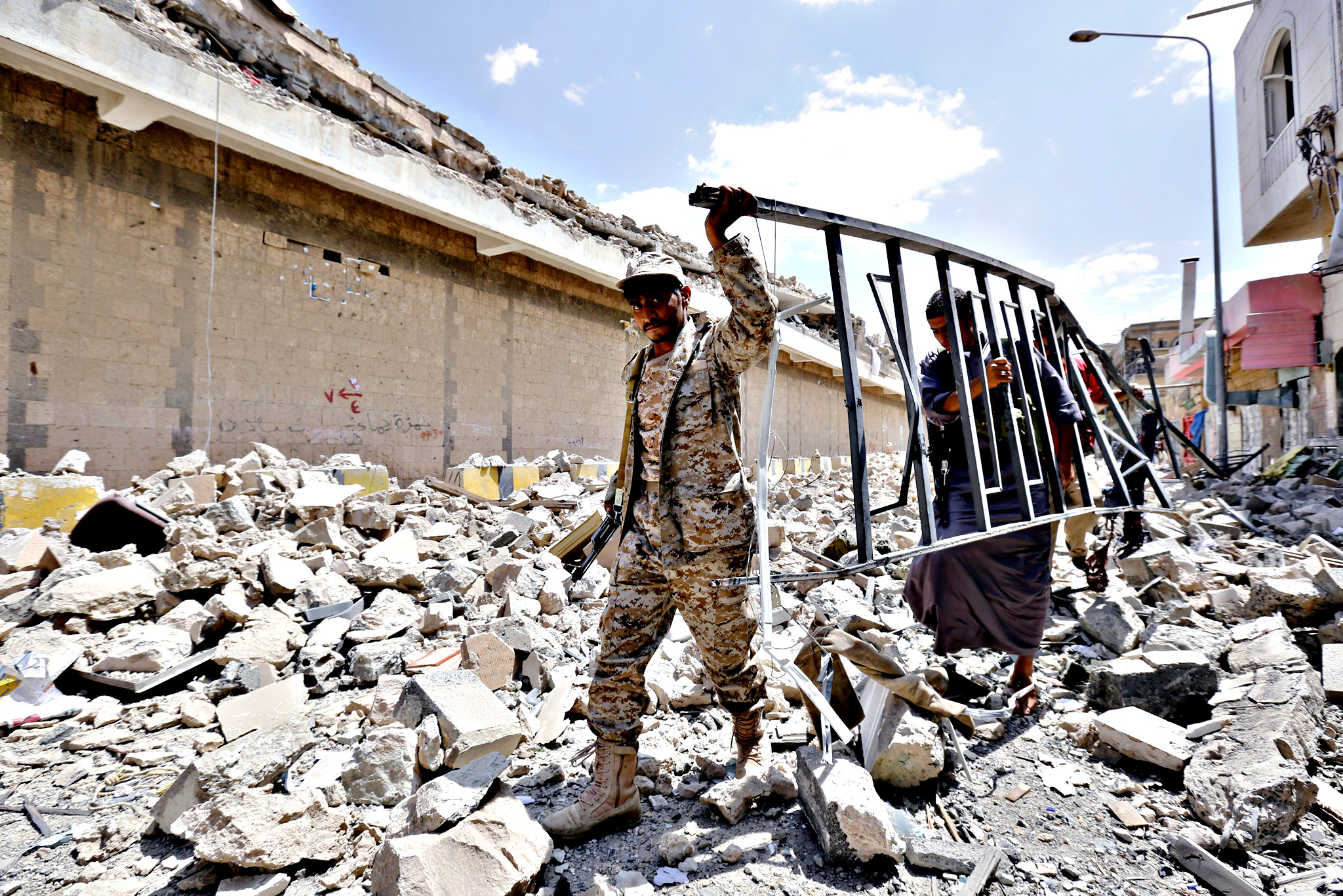 A member of the Yemeni armed forces and a member of the Houthi militia remove debris from amid the rubble of the Houthi-controlled headquarters of Yemen s Defence Ministry, destroyed by airstrikes carried out by the Saudi-led coalition in Sana a, Yemen, 16 September 2015. Yemen has seen six months of intense conflict since the Houthis advanced from Sana'a on the southern city of Aden, forcing Abd Rabu Masour Hadi to flee the country to Saudi and precipitating the ongoing coaltion military operations in the impoverished country. According to reports Hadi has refused to attend a new round of ceasefire negotiations unless the Houthis publicly recognise the legitimacy of the exiled Government and withdraw from Yemen's main cities