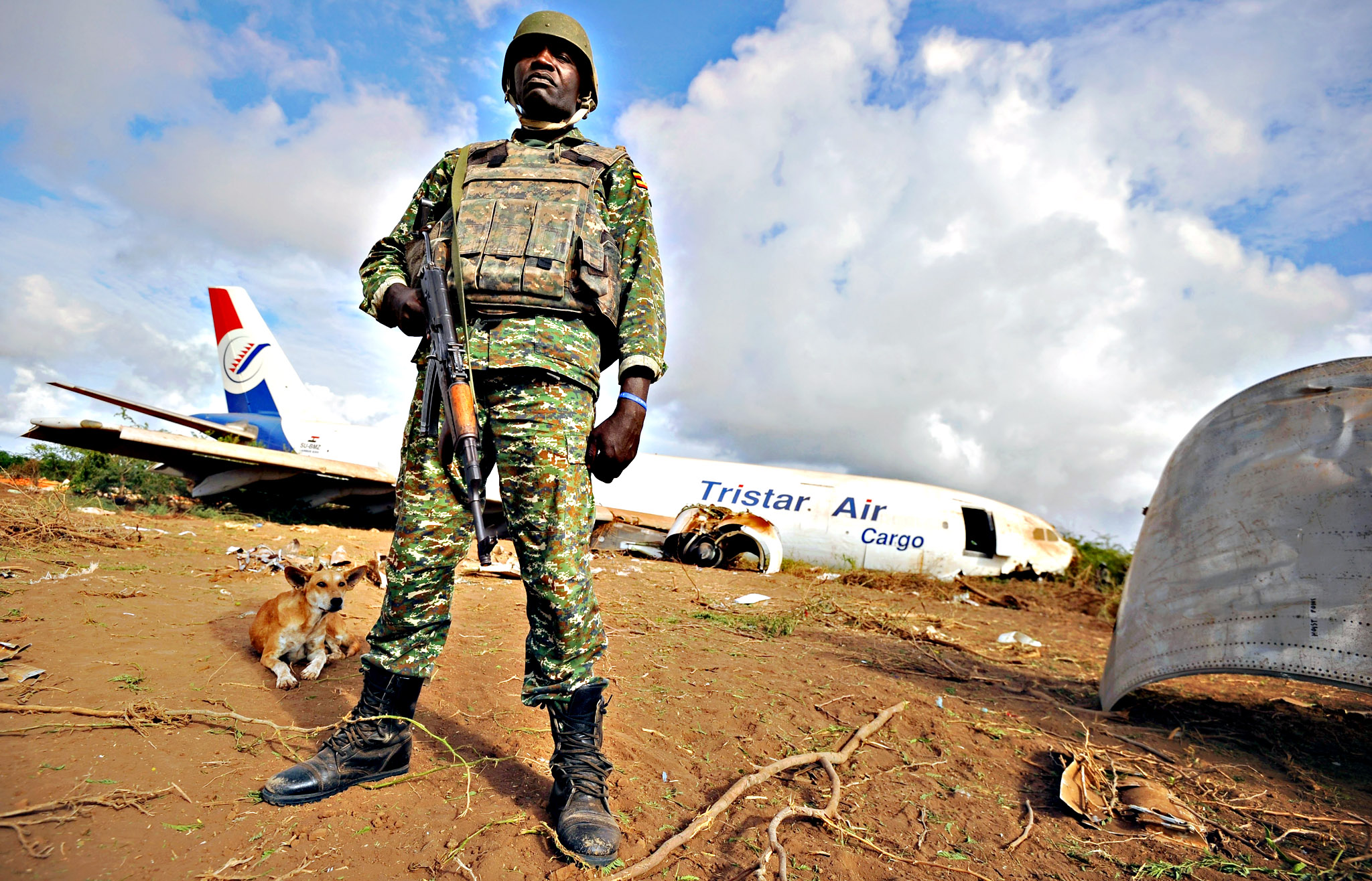A soldier from the African Union (AU) peacekeeping force stands guard at the site where a cargo plane carrying supplies for AU troops crash-landed outside Somalia's capital, on Tuesday at Abirska, some 18 kilometres outside Somalian capital, Mogadishu. The officials said the Egyptian-owned transport plane went down after making several unsuccessful passes over the seafront airport. Two of the six crew members suffered light injuries in the crash, the officials said, but added that the plane and those on board were safe having landed in an area controlled by the Somali government and the African Union's AMISOM force