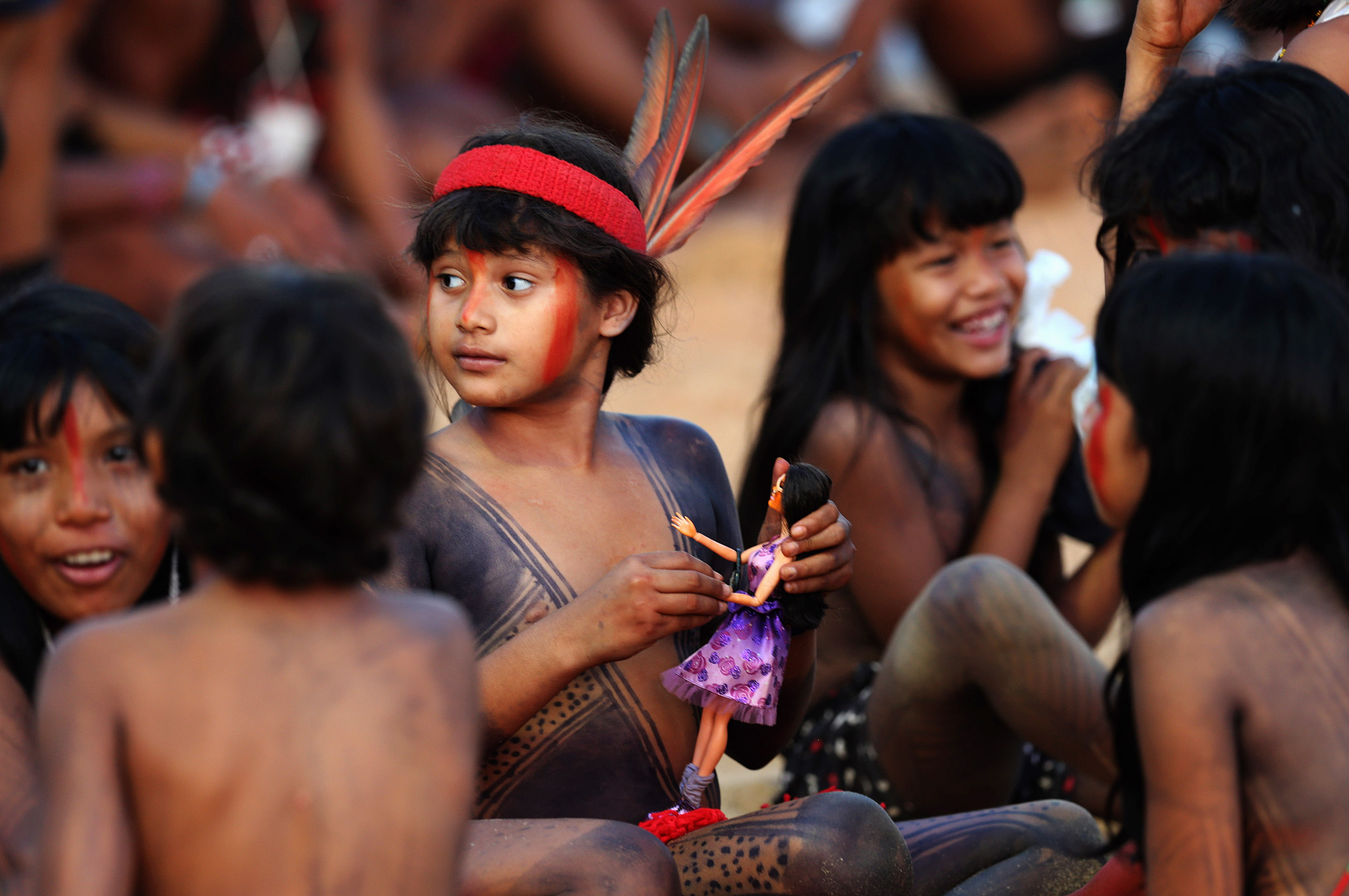 Gaviao children play with a Barbie doll during the World Indigenous Games, in Palmas, Brazil, Monday, Oct. 26, 2015.  The Games have been hampered by technical hick-ups and allegations of mismanagement and poor organization. On opening day, construction workers were still busily buzzing away on the installations, and some participants have complained of poor conditions in the indigenous lodgings, which the press was forbidden from visiting. (AP Photo/Eraldo Peres)