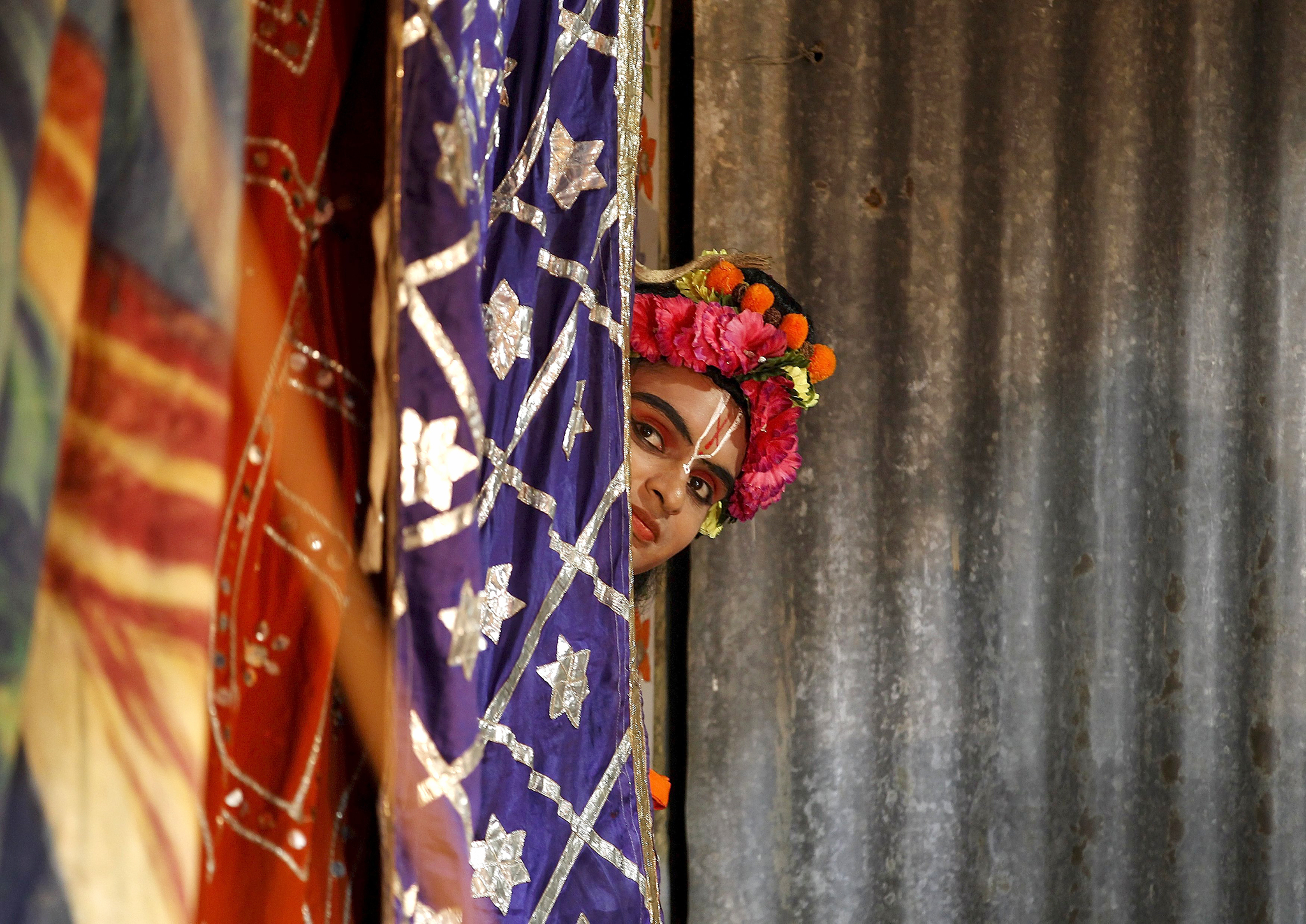 "An artist peeps out as he waits backstage to take part in the Ramlila performance, a re-enactment of the life of Hindu Lord Rama, ahead of Dussehra in Ahmedabad...An artist peeps out from behind a curtain as he waits backstage to take part in the Ramlila performance, a re-enactment of the life of Hindu Lord Rama, ahead of Dussehra in Ahmedabad, India, October 19, 2015. Effigies of the 10-headed demon king ""Ravana"" are burnt on Dussehra, the Hindu festival that commemorates the triumph of Lord Rama over the Ravana, marking the victory of good over evil. Dussehra is celebrated on October 22.  Picture taken October 19, 2015. REUTERS/Amit Dave"