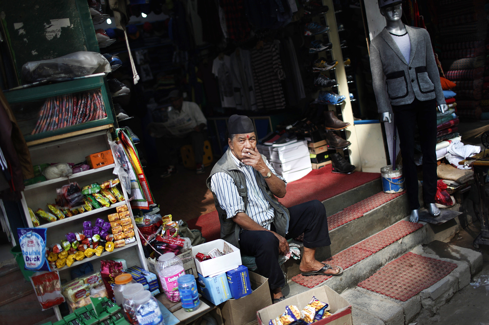 A Nepalese man waits for customers at his shop in Kathmandu, Nepal, Thursday, Oct. 1, 2015. Indian trucks carrying food and fuel began trickling into Nepal on Wednesday, a welcomed development for a nation grappling with shortages caused by a blockade during protests against the country's new constitution. Nepal has restricted the movement of vehicles due to the fuel shortages, with cars permitted to run only on alternate days. (AP Photo/Niranjan Shrestha)