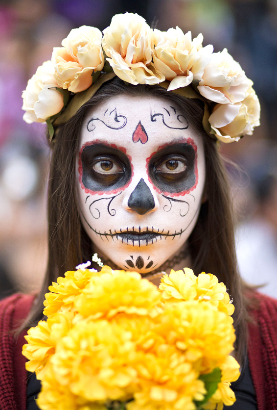 "A young girl with her face painted as a ""Catrina"" takes part in a Day of the Dead celebration in Mexico City, Sunday, Oct. 25, 2015. The ""Catrina,"" a figure of a skeleton wearing an elegant broad-brimmed hat was first done as a satirical engraving by artist Jose Guadalupe Posada sometime between 1910 and his death in 1913. (AP Photo/Esteban Felix)"