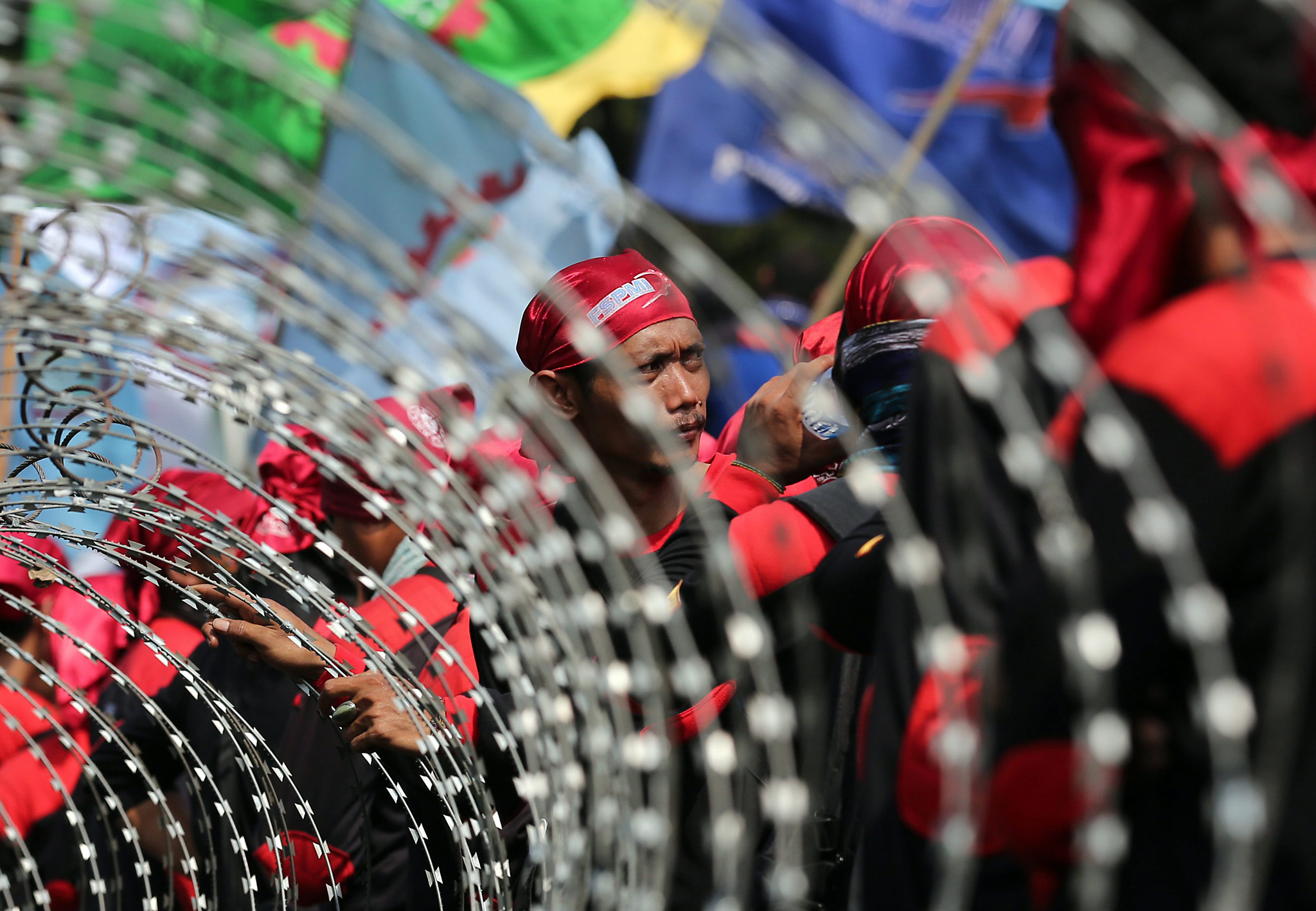 Labour Protest in Jakarta...epa05003108 Indonesian workers stands near barbed wire during a rally outside the Presidential Merdeka Palace in Jakarta, Indonesia, 30 October 2015. Thousands of workers staged a rally urging the government to improve working conditions and protest against job cuts.