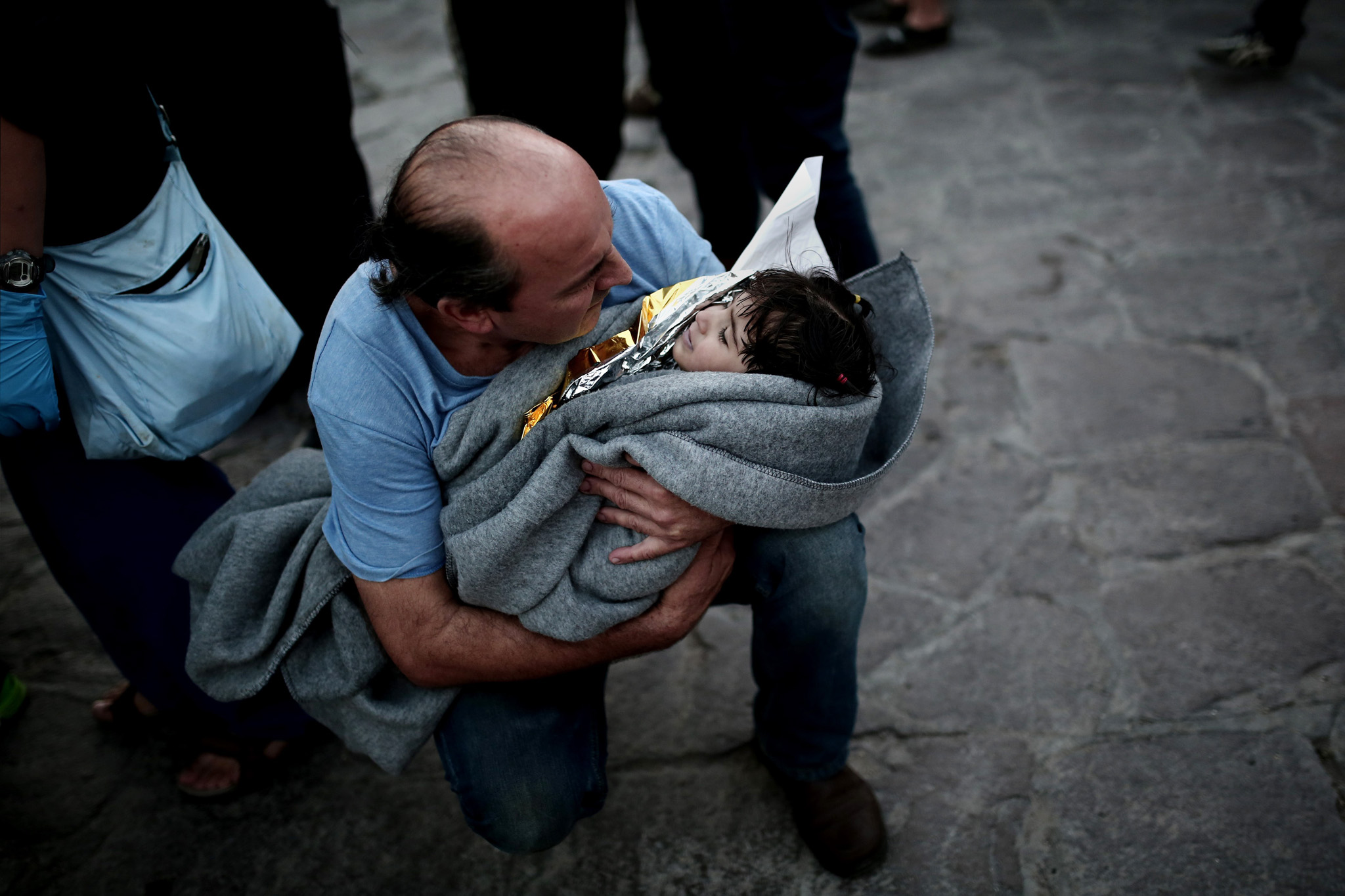 A man holds a child after a boat with refugees and migrants sunk while attempting to reach the Greek island of Lesbos from Turkey, on October 28, 2015. At least five migrants including three children, died on October 28, 2015 after four boats sank between Turkey and Greece, as rescue workers searched the sea for dozens more, the Greek coastguard said. The new accidents brought to 34 the number of migrants found dead in Greek waters this month, according to an AFP tally based on data from Greek port police. Since the start of the year, 560,000 migrants and refugees have arrived in Greece by sea, out of over 700,000 who have reached Europe via the Mediterranean, according to the International Office for Migration (IOM). AFP PHOTO / ANGELOS TZORTZINISANGELOS TZORTZINIS/AFP/Getty Images