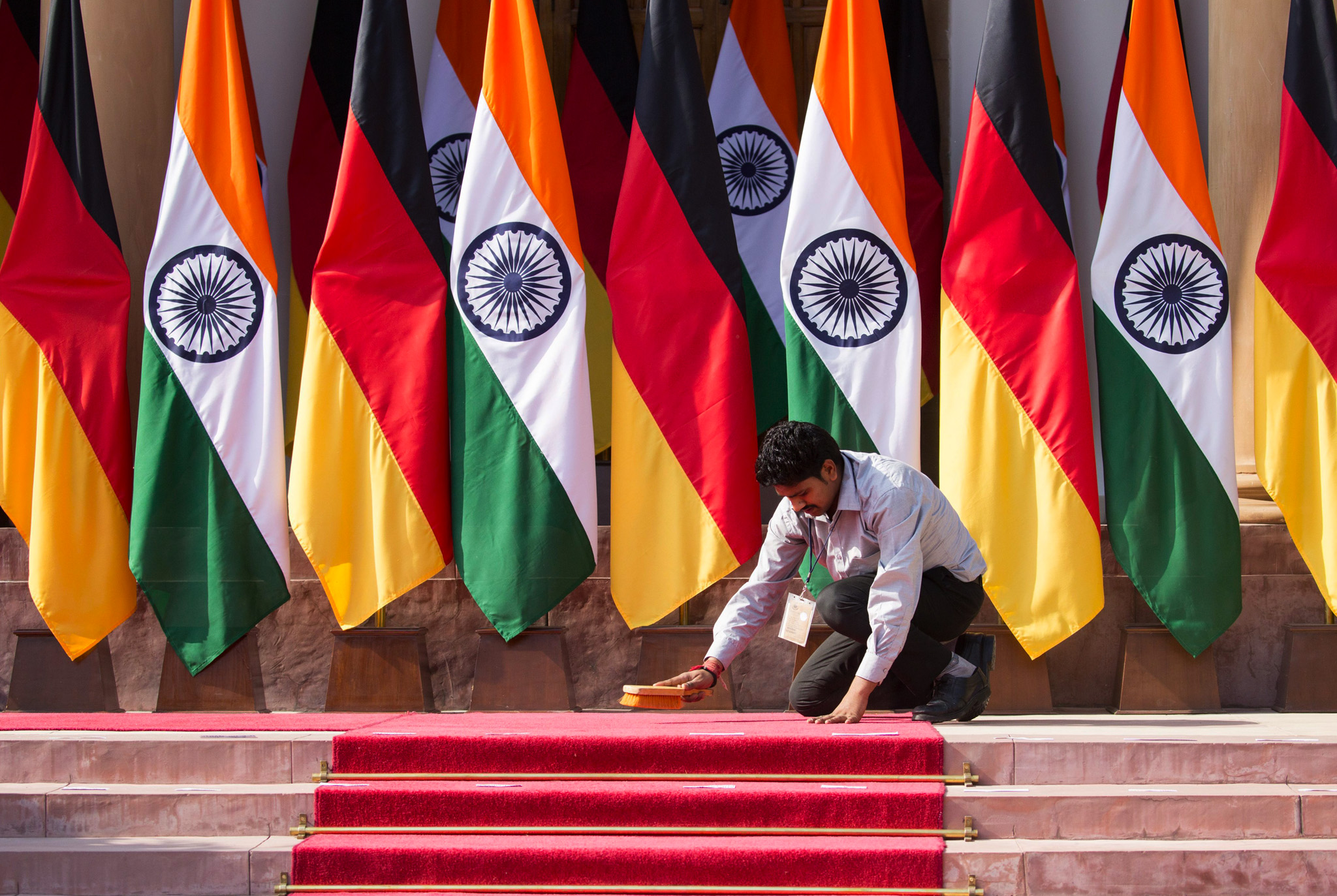 A member of staff cleans the red carpet at the Hyderabad House of Indian Prime Minister Narendra Modi for a group picture after the third Indian-German intergovernmental consultations in New Dehli, India.