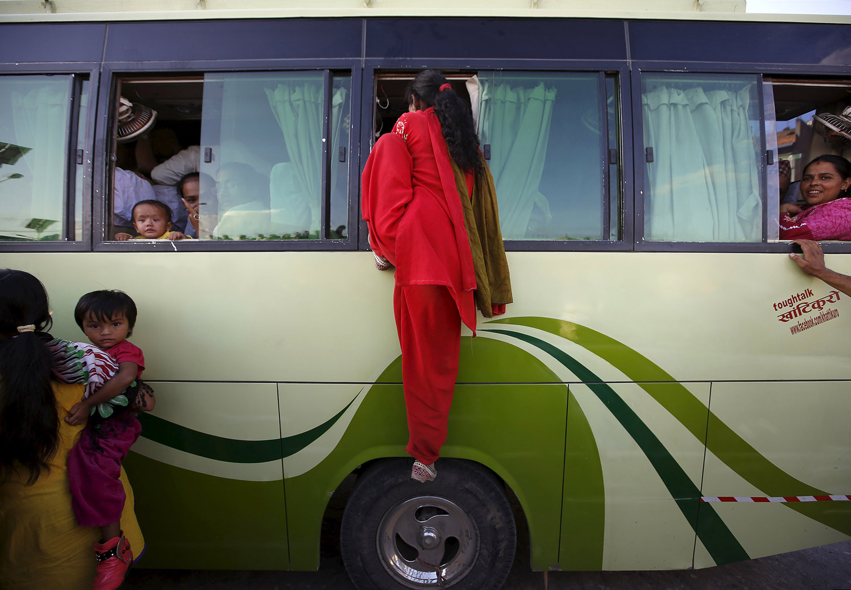 A passenger climbs through the window of an overcrowded bus