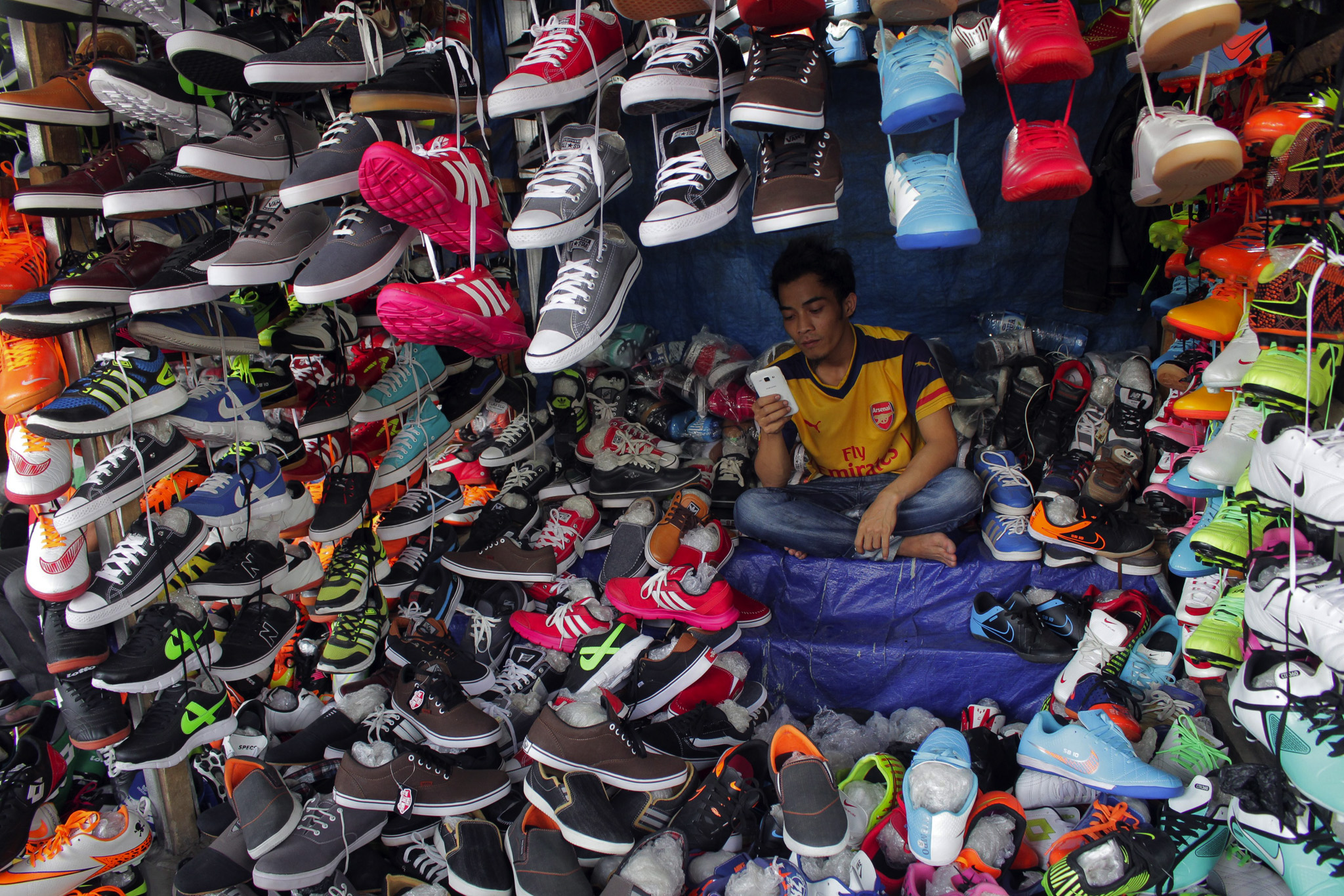A shoe seller waits for customers at a market in Bogor, Indonesia
