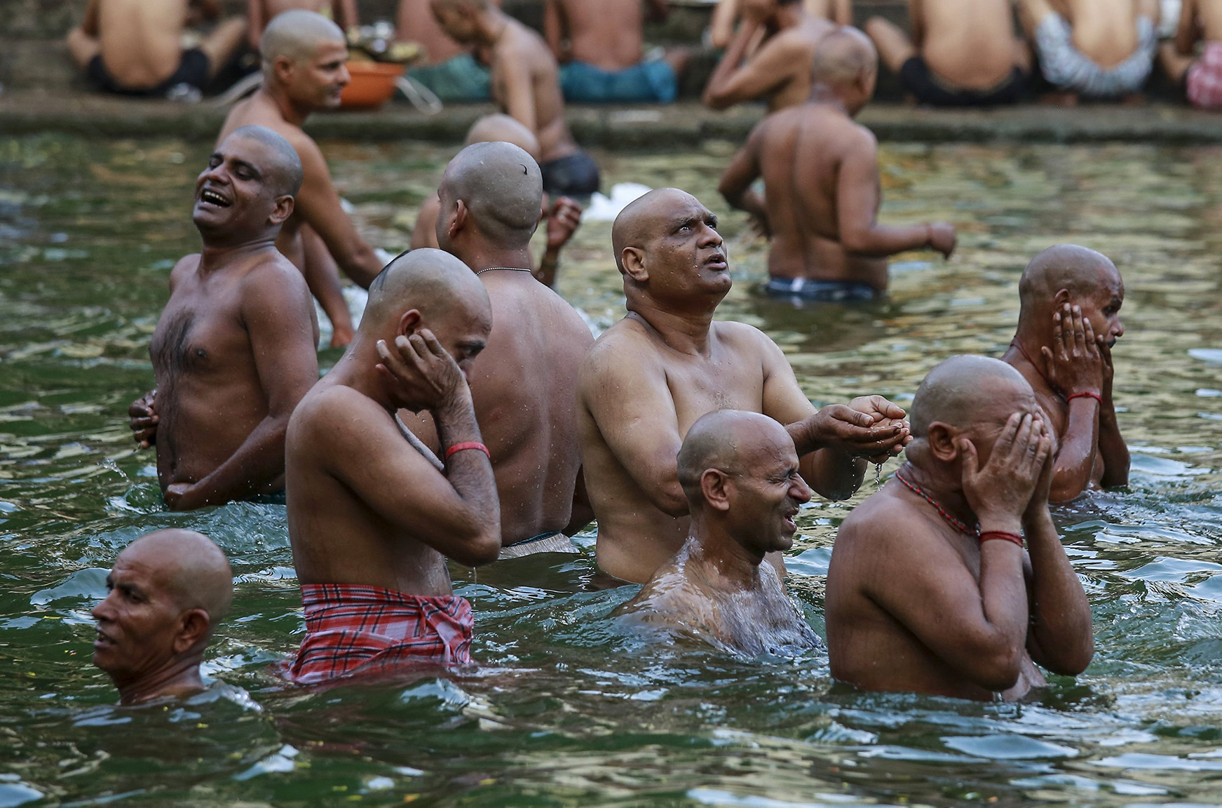 Hindu devotees pray in a holy pond on the auspicious day of Mahalaya in Mumbai