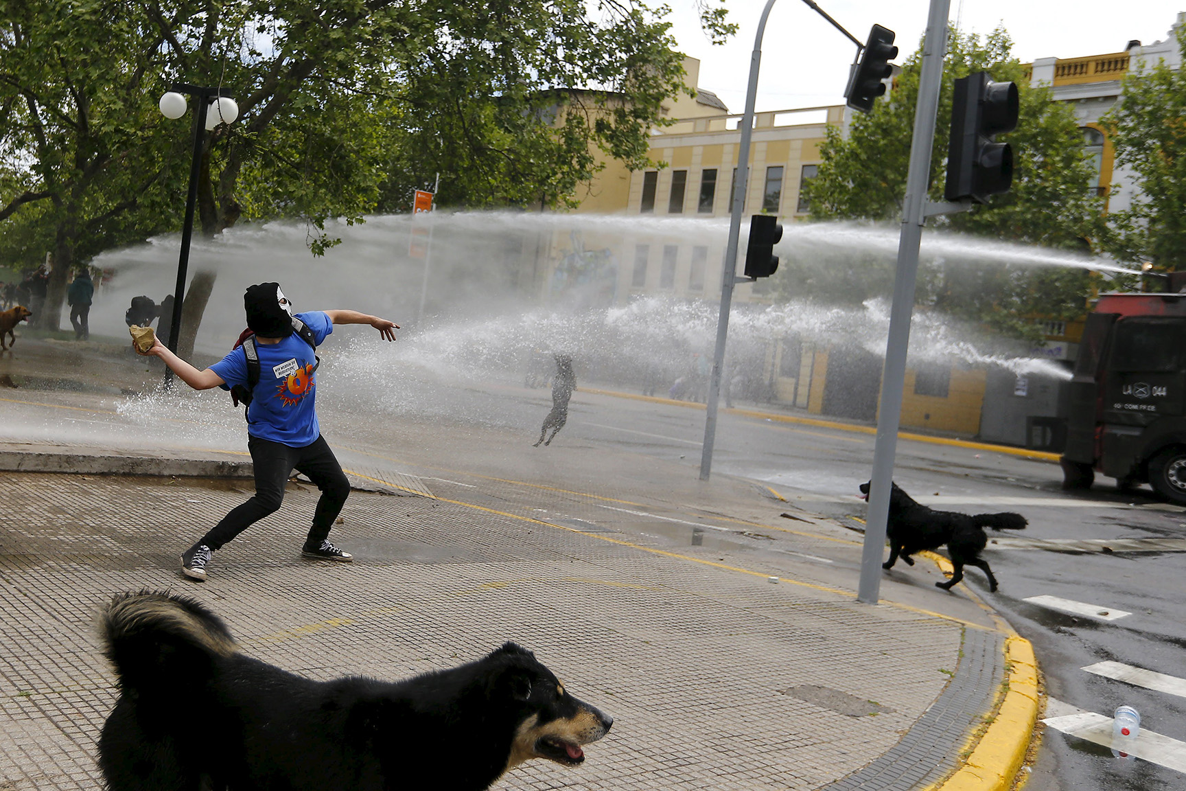 A Mapuche Indian activist prepares to throw a stone at riot police vehicle during a protest march against Columbus Day in downtown Santiago