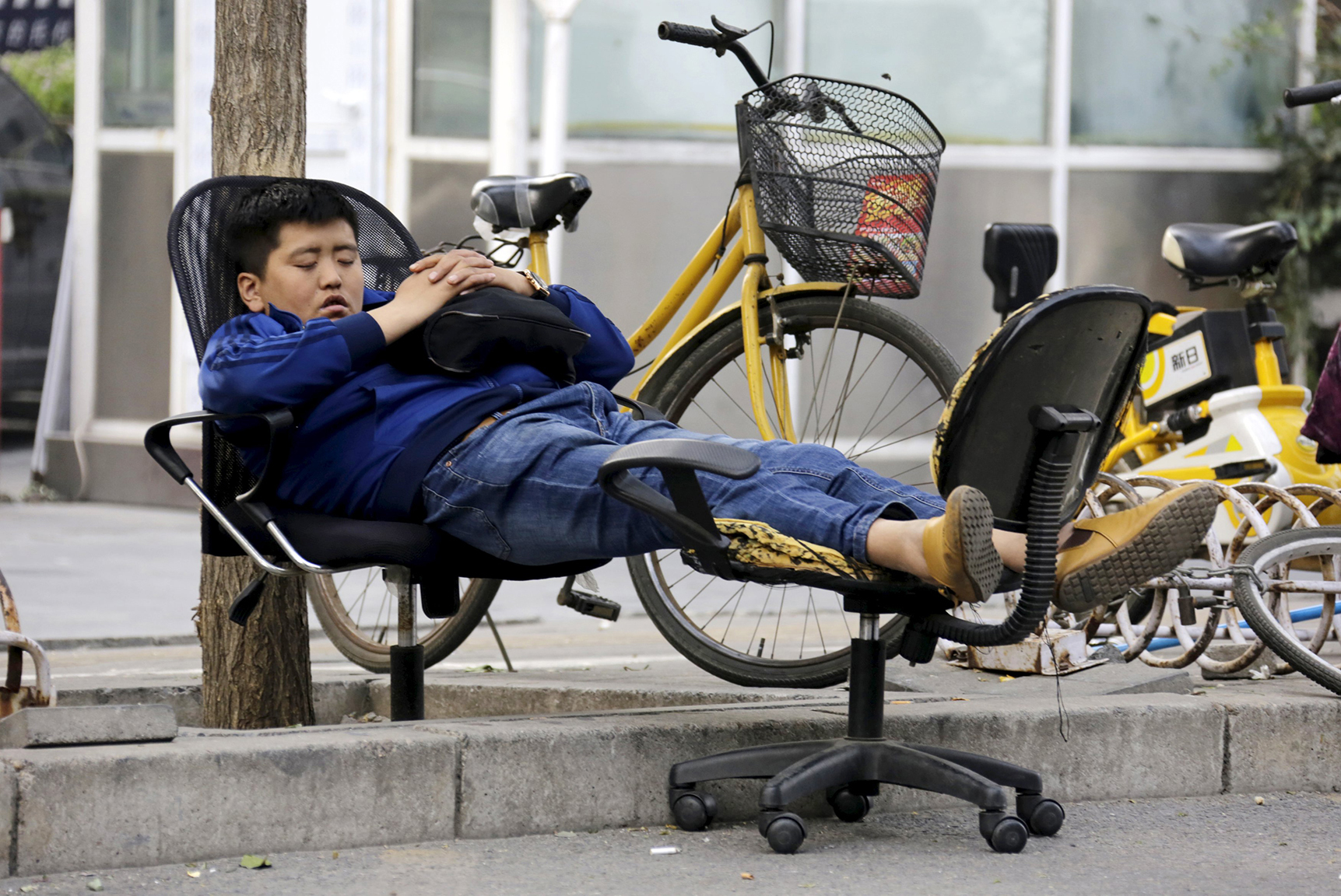 A man sleeps on two chairs beside a road in Beijing
