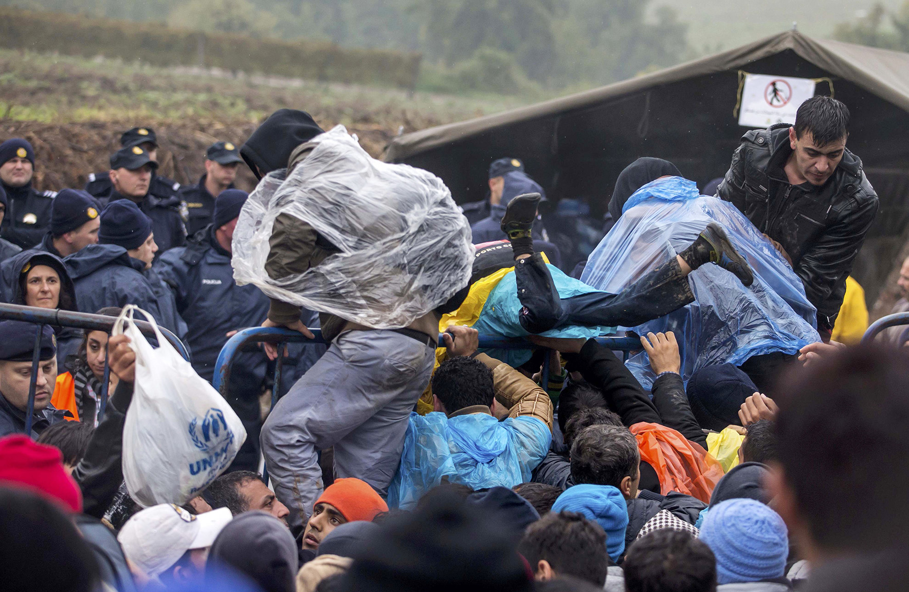Migrants jump over a fence as they attempt to cross the Croatian border near the village of Berkasovo