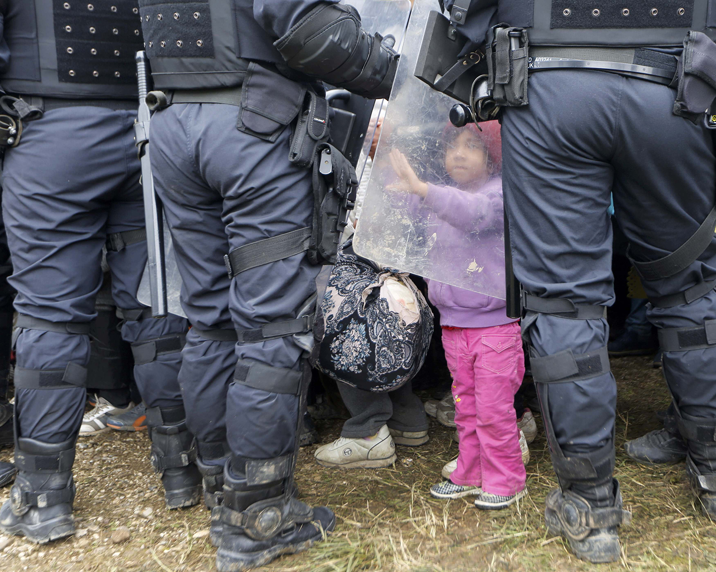 Young girl touches riot shield of police officer as she and other migrants walk after crossing border in Rigonce