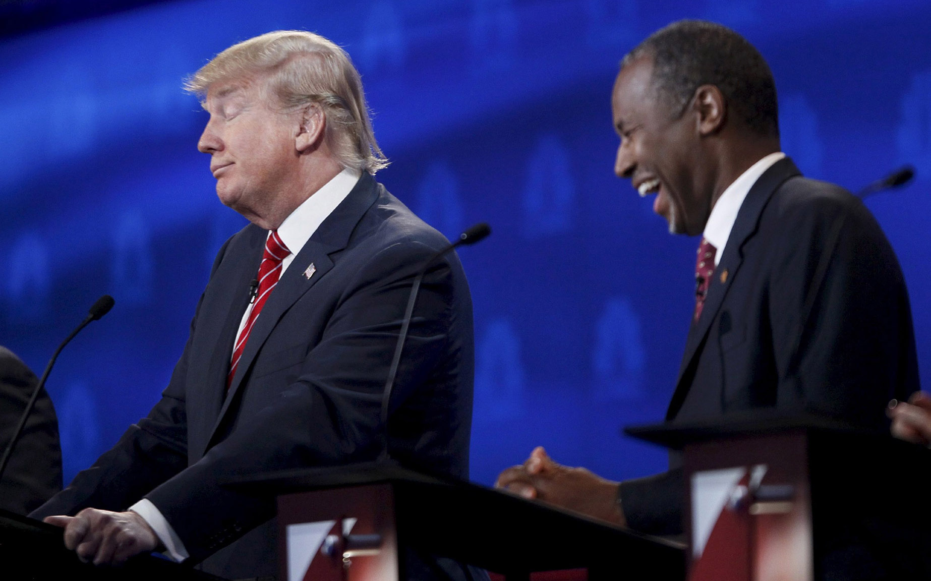 Republican U.S. presidential candidate Carson laughs at an answer from Trump at the 2016 U.S. Republican presidential candidates debate held by CNBC in Boulder