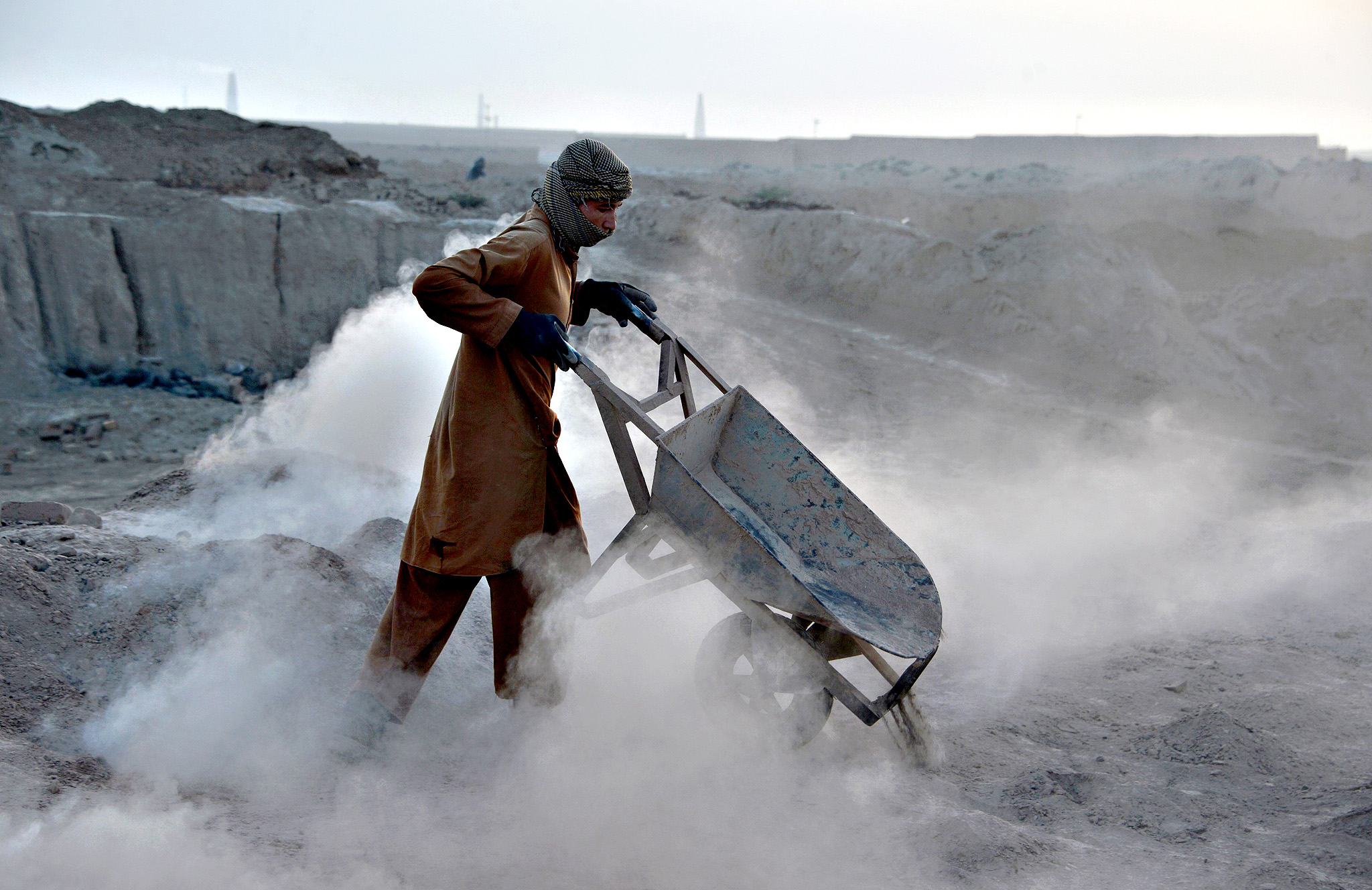An Afghan labourer pushes his wheelbarrow at a brick factory on the outskirts of Kabul on October 8, 2015