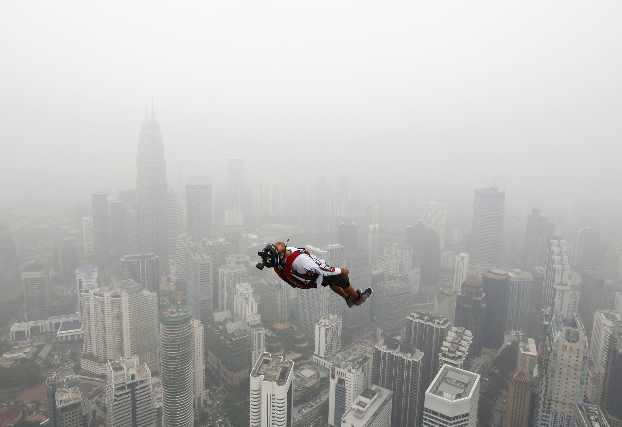 BASE jumper leaps from the 300-metre high Kuala Lumpur Tower during the International Tower Jump in which more than 100 people take part, on a hazy day in Kuala Lumpur, Malaysia October 2, 2015. Slash-and-burn agriculture in neighbouring Indonesia has blanketed Malaysia and Singapore in a choking haze for weeks.
