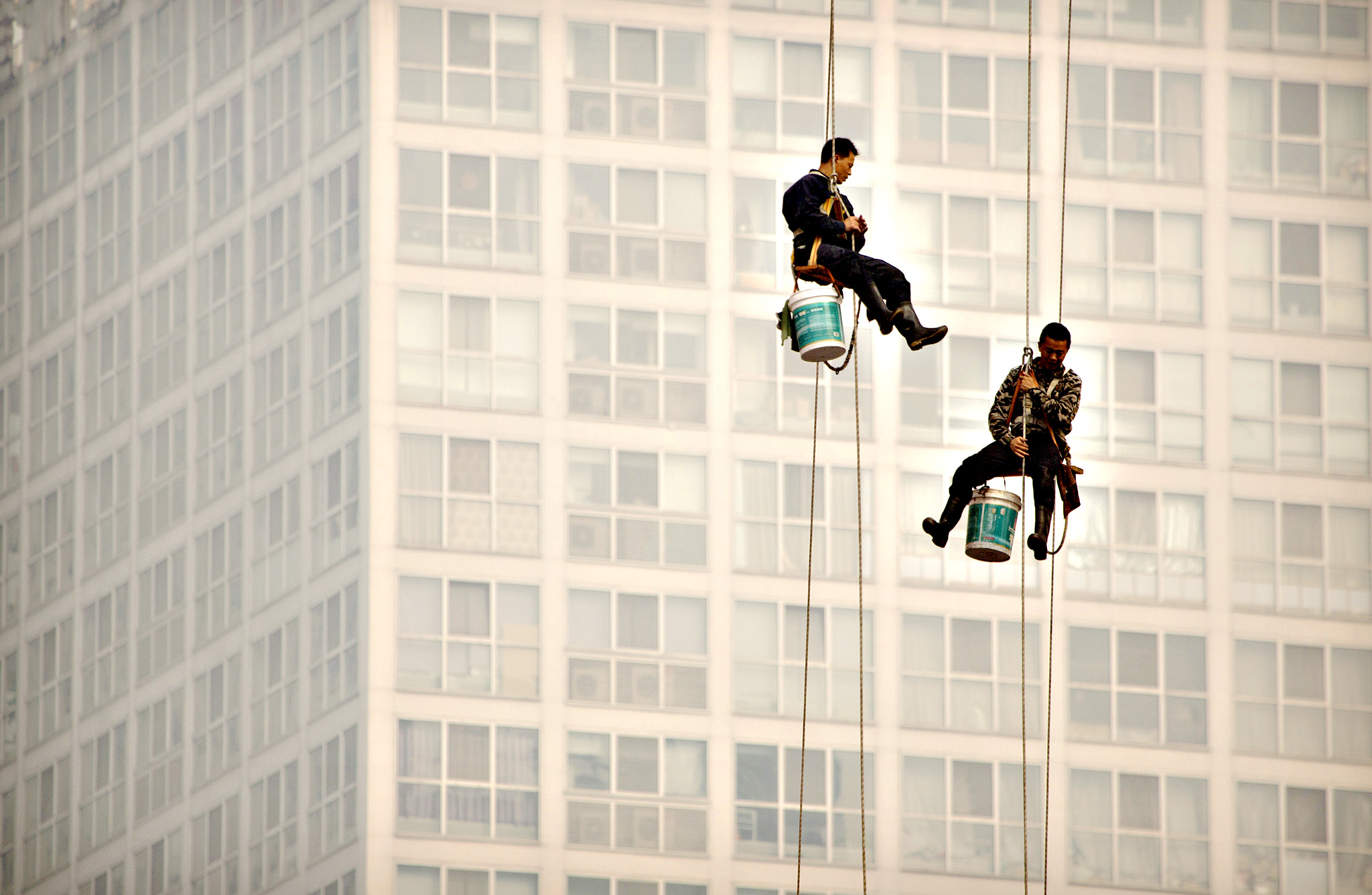 Window washers use cables to lower themselves from a skyscraper while working on a polluted day in Beijing, Tuesday, Oct. 6, 2015. Air quality readings in the city on Tuesday were at levels considered hazardous by international measuring standards