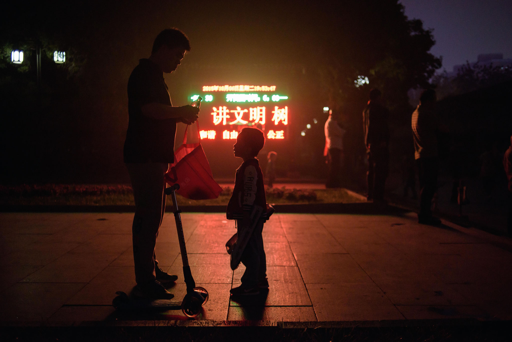 A man opens a drink to a child as they stand before a display board at the entrance to a park in Beijing