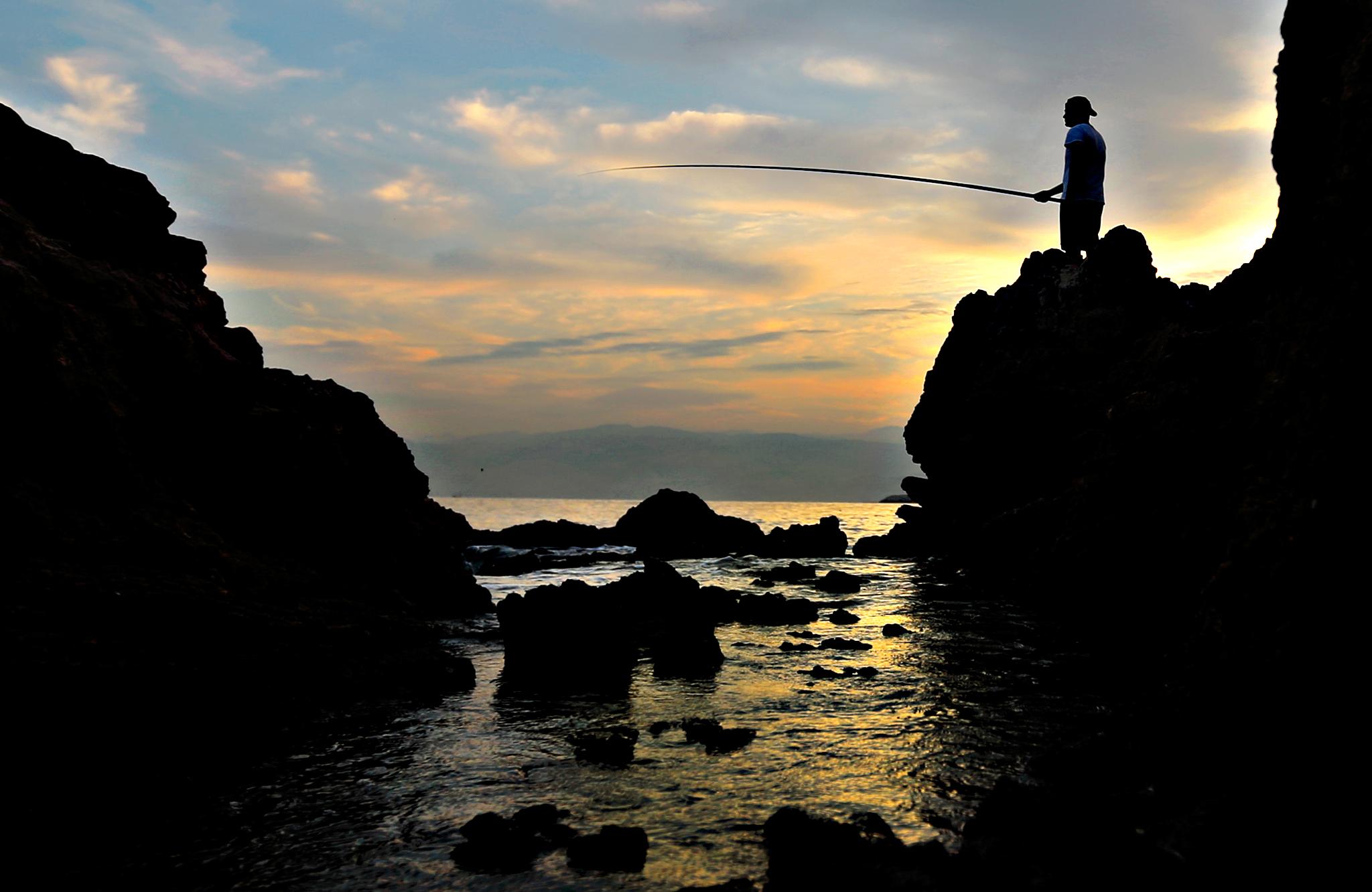 A Lebanese angler casts his fishing pole from a rocky coastal area along the Beirut coastline as the sun rises over the Mediterranean Sea, Lebanon, Tuesday, Oct. 6, 2015