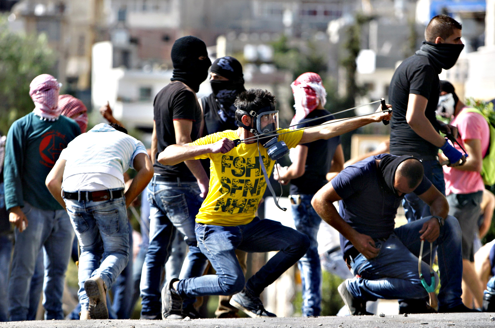 A Palestinian uses a slingshot to throw stones at Israeli troops during clashes in the West Bank city of Bethlehem on Wednesday. Seven Israelis and 30 Palestinians, including children and assailants, have been killed in two weeks of bloodshed in Israel, Jerusalem and the occupied West Bank. The violence has been partly triggered by Palestinians' anger over what they see as increased Jewish encroachment on Jerusalem's Al-Aqsa mosque compound, also revered by Jews as the site of two destroyed Jewish temples.
