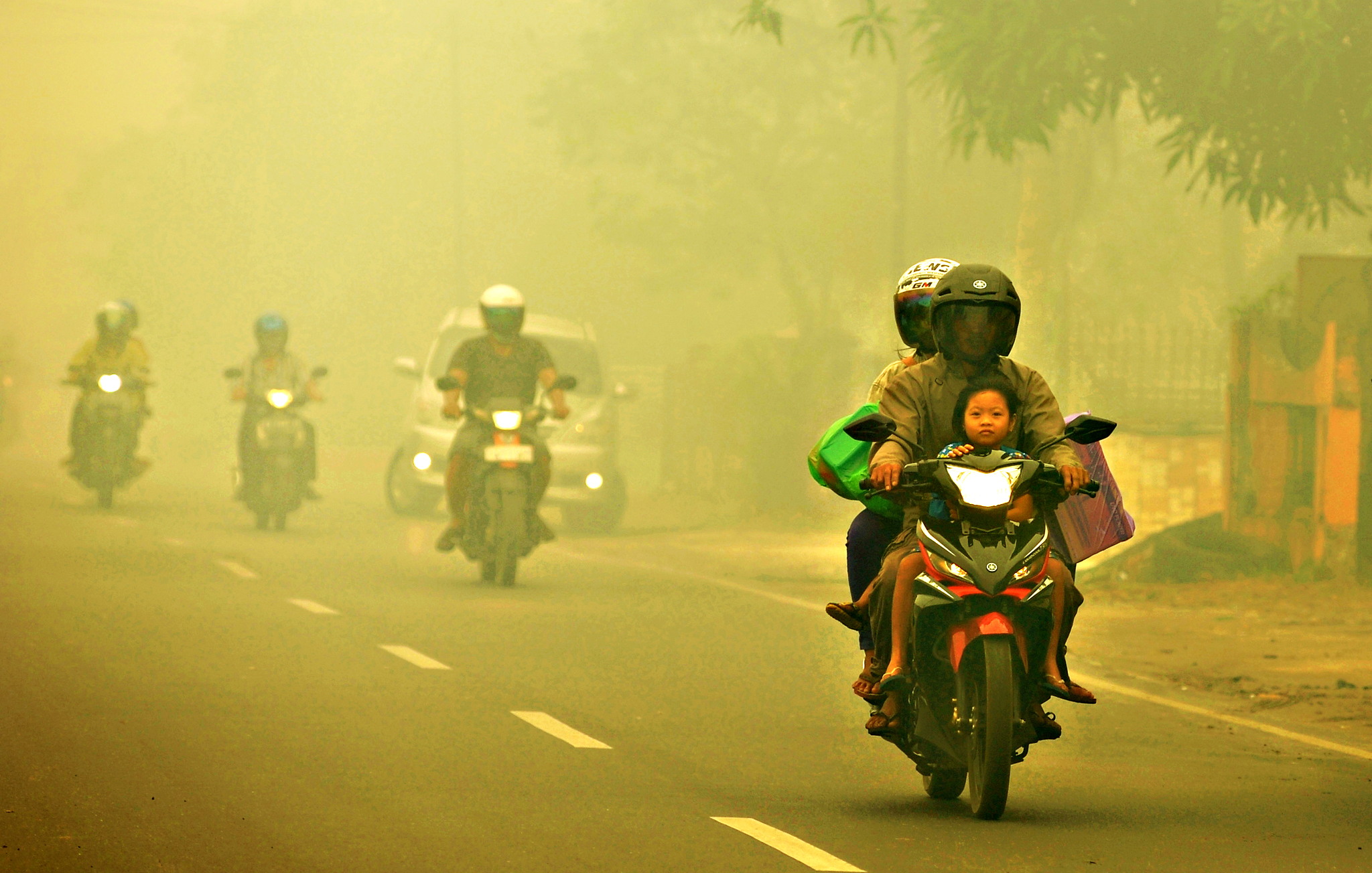 Motorists ride on a road as thick haze from forest fires shroud the city in Palangkaraya, Central Borneo, Indonesia, Tuesday, Oct. 27, 2015. The haze has blanketed parts of western Indonesia for about two months and affected neighboring countries like Singapore, Malaysia and Thailand