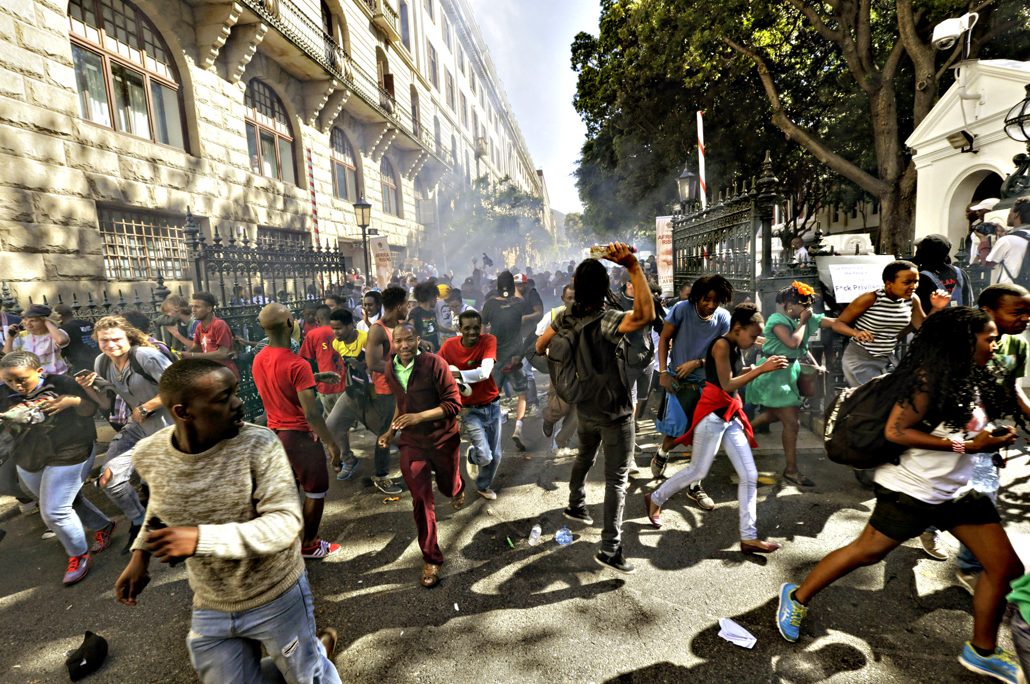 Protesting university students flee as police fire stun grenades outside Parliament in Cape Town, South Africa, Wednesday Oct. 21, 2015. The protests are part of a wave of nationwide protests that have shut down many South Africa universities, which say they are struggling with higher operational costs as well as inadequate state subsidies.